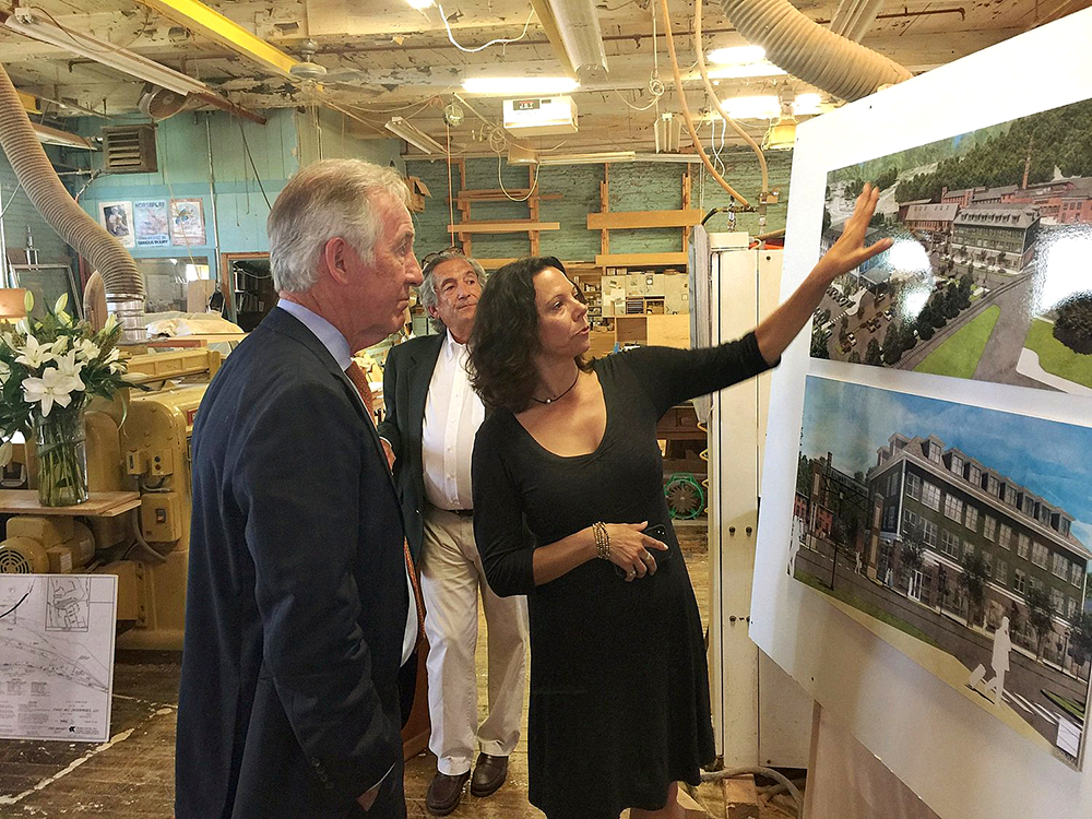 Leigh Davis, director of development for Eagle Mill Redevelopment, shows U.S. Rep. Richard Neal, D-Springfield, plans to turn the former paper mill complex in Lee into a housing, marketplace and commercial area with a nearby hotel, as they tour the site Tuesday. The proposed $60 million project steadily has received reinforcement with public money for the repurposing of three buildings. HEATHER BELLOW - THE BERKSHIRE EAGLE