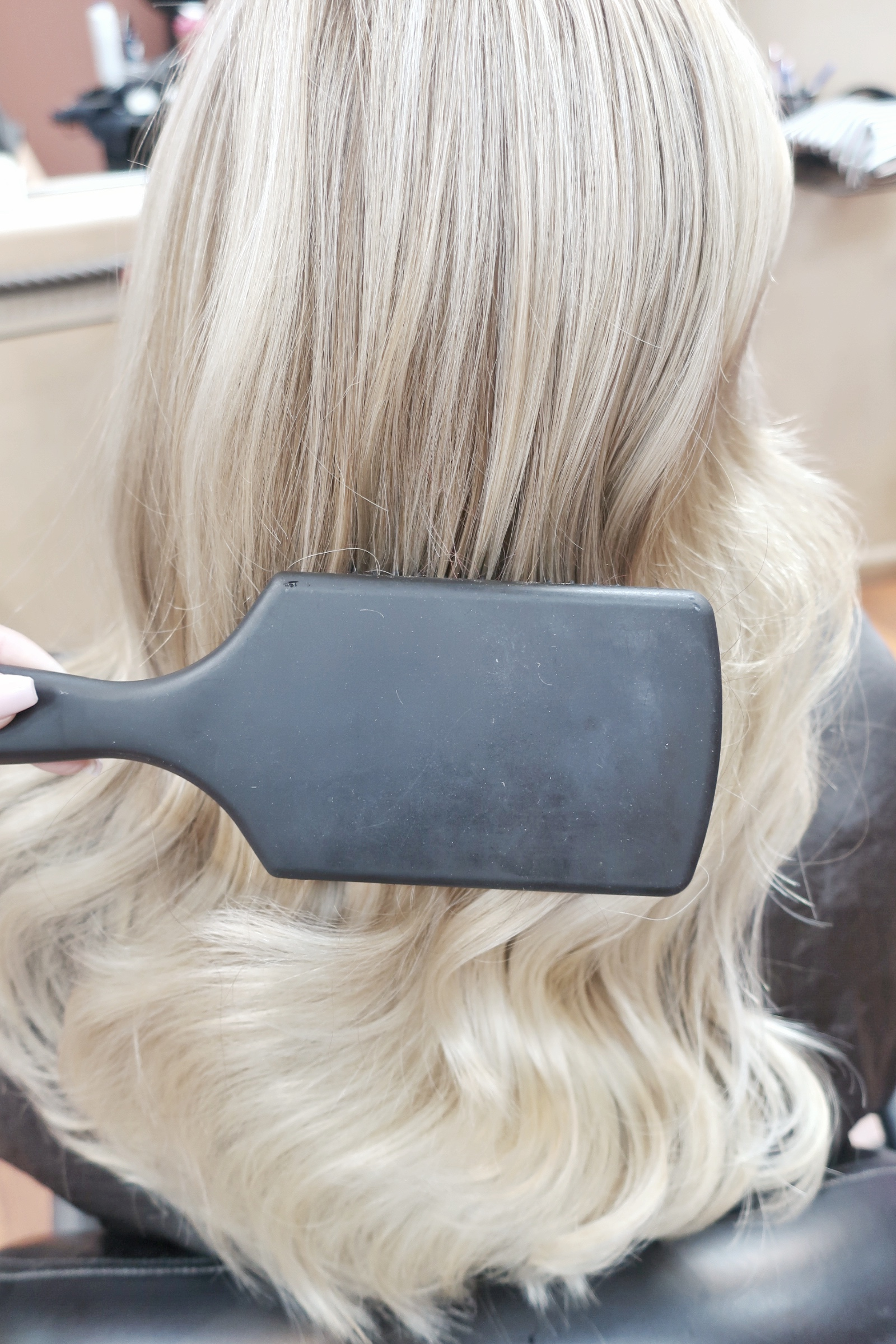 Next spray brush with hairspray and brush curls down and gently. (as shown in photo)