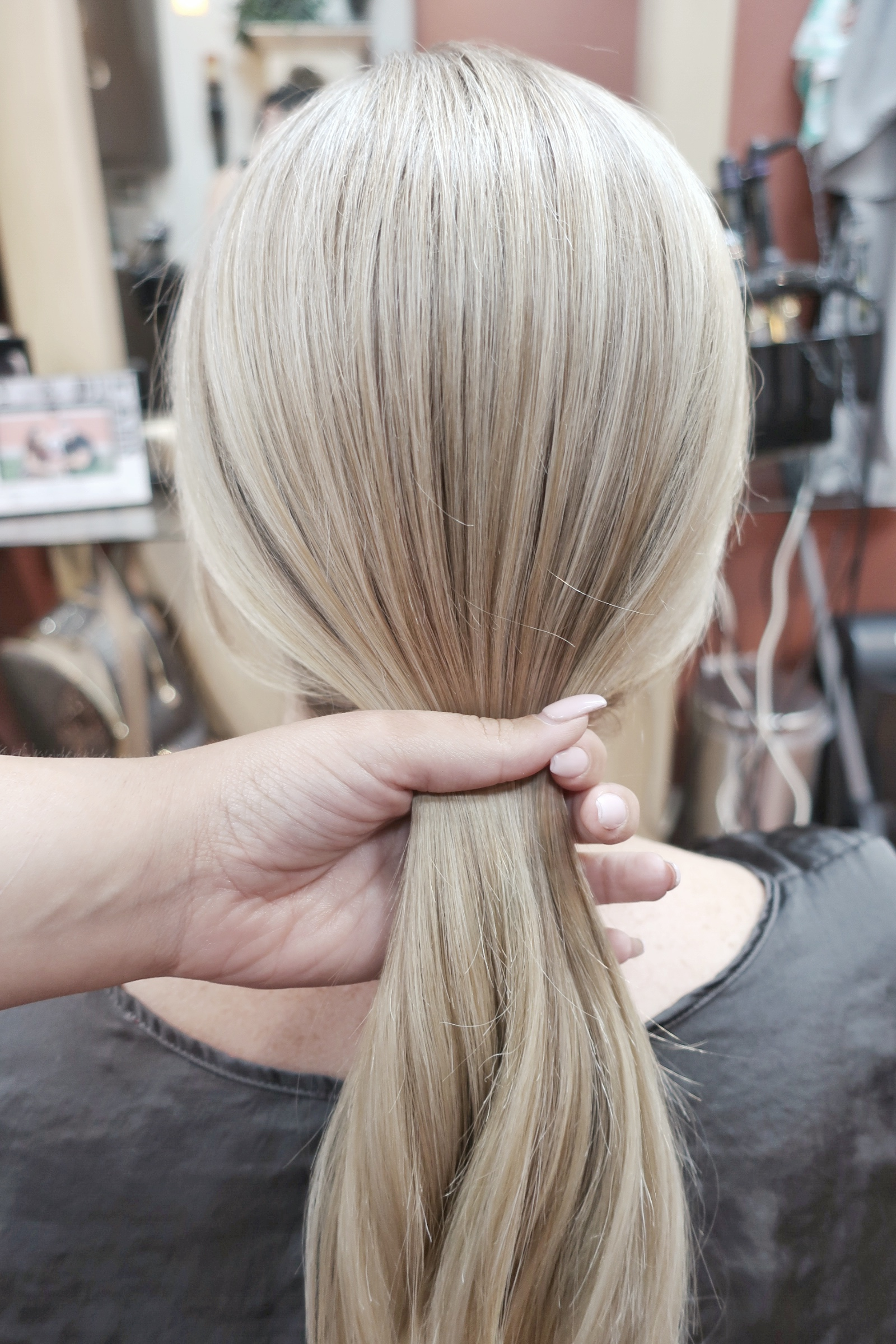 Smooth hair into a low pony