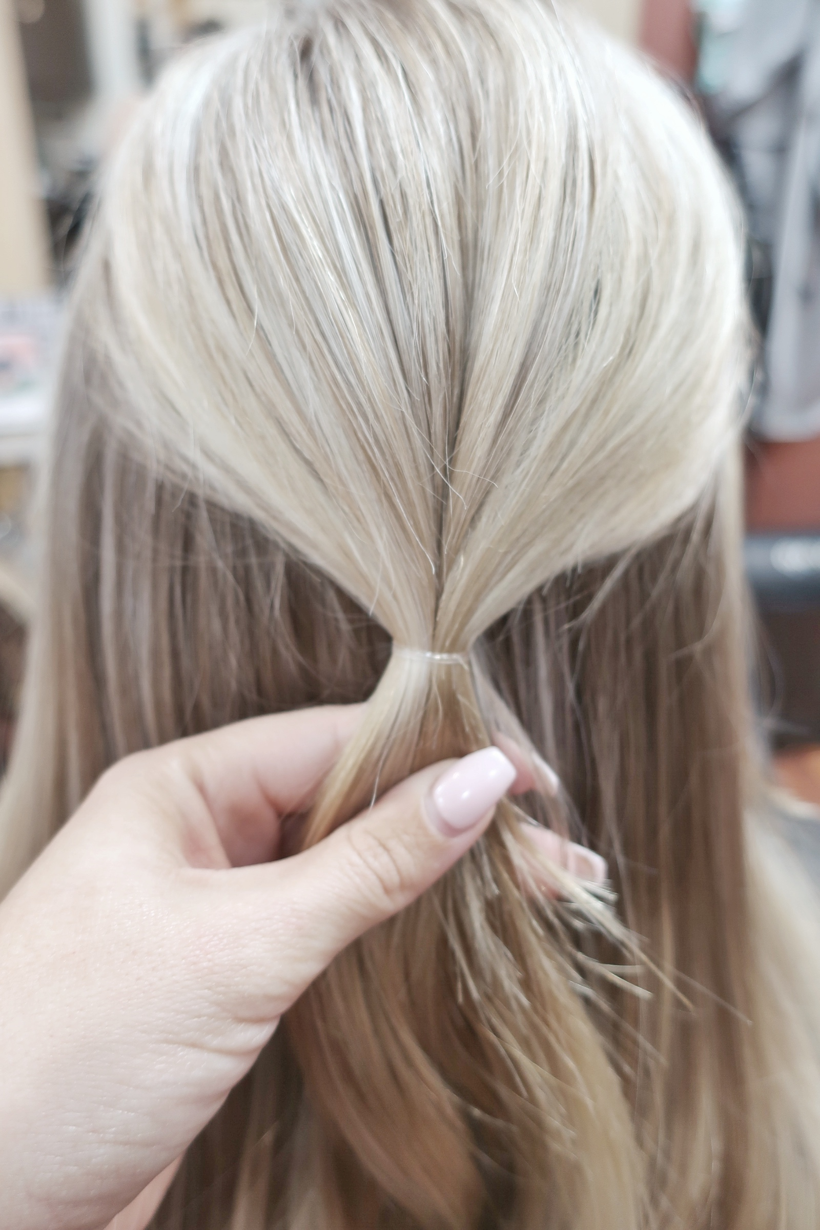 Gather HALF hair and put into a half up securing with a no snag elastic. Make sure before securing hair tie that hair is smooth and any fringe around your face you would like left out is.