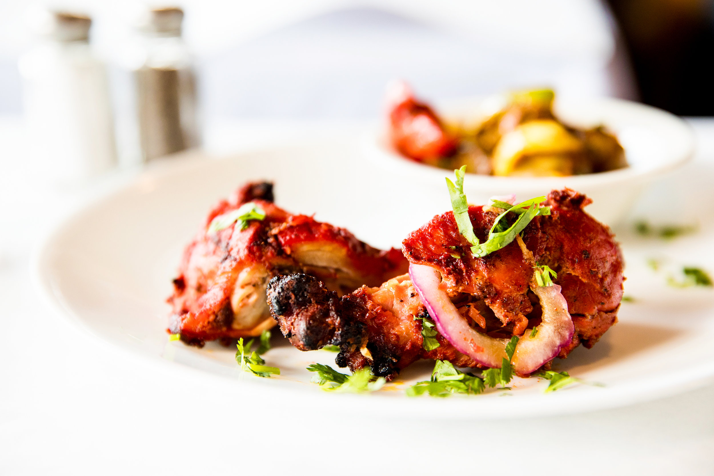Tandoori Chicken - Juicy spring half chicken marinated in yogurt, fresh ground spices and saffron and served with sliced onions and lemons. $14