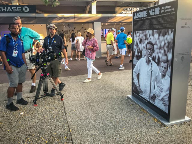 An ESPN crew tapes some of the imagery. Shots of the exhibition were used throughout the US Open broadcasts.