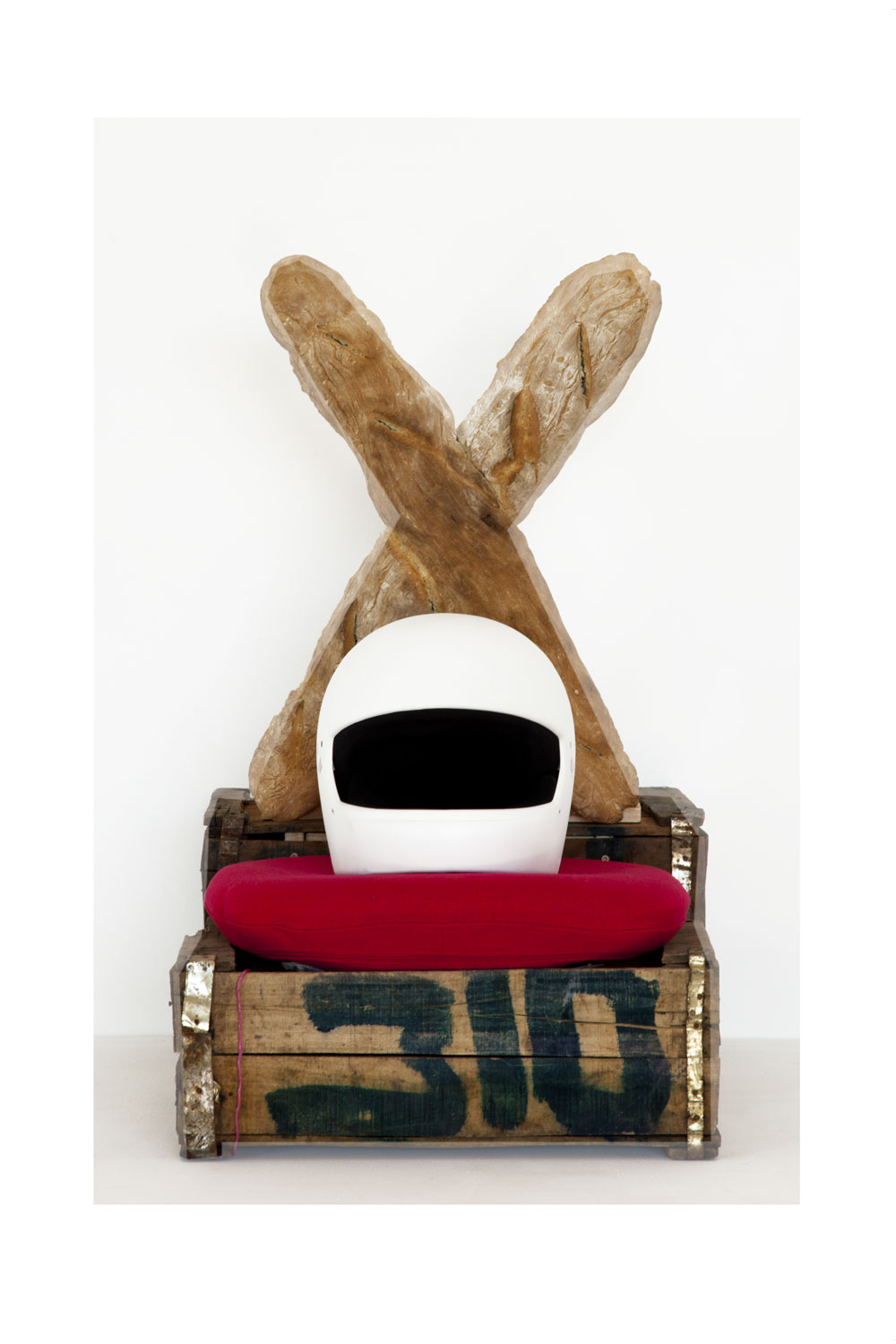 Sculpture (crate, helmet, seat cushion, bread)