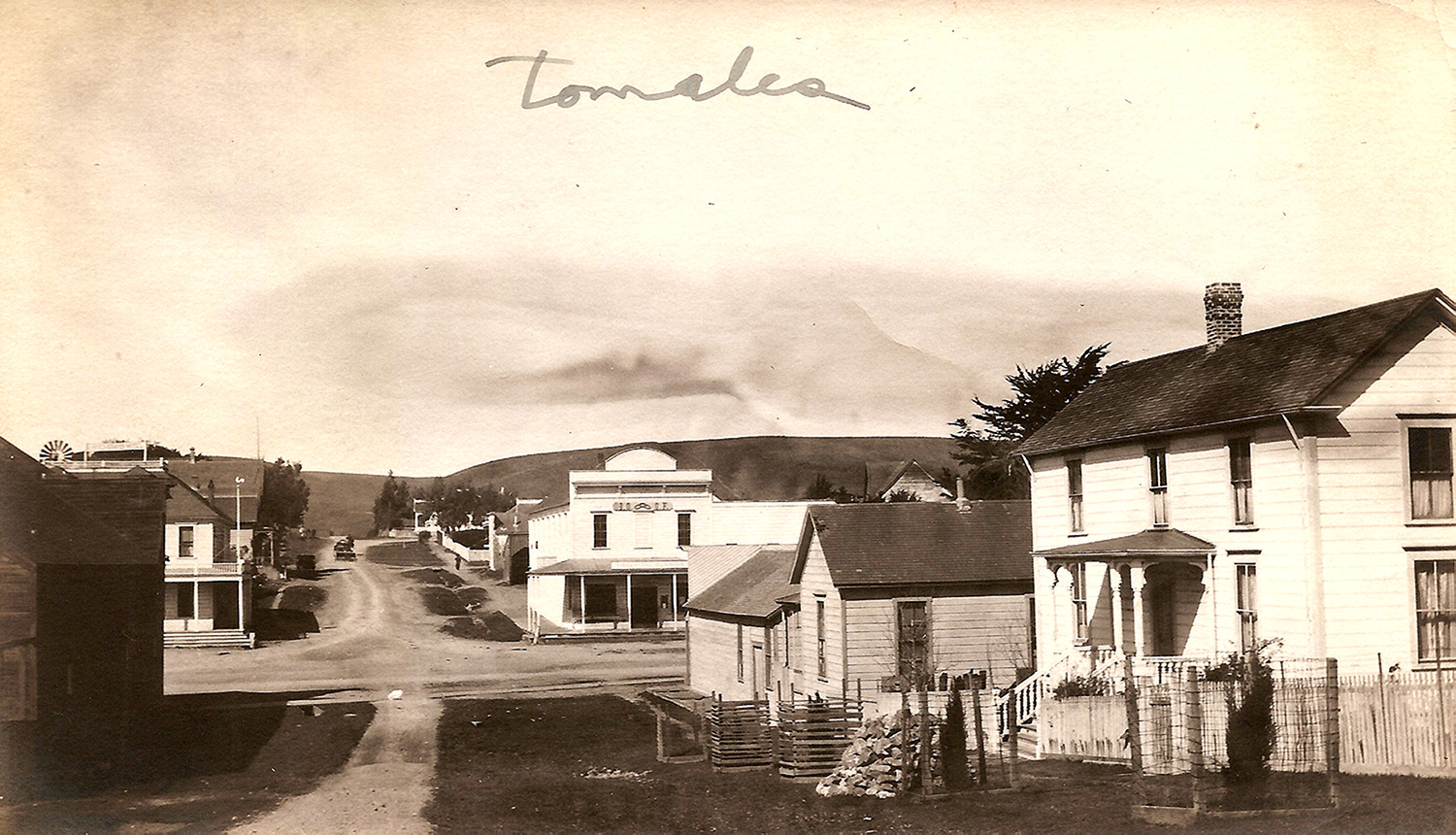 A view west from First Street across Highway One, Upper Town Tomales's main intersection, a few years before a large fire destroyed sixteen buildings, including the hotel on the corner, one just visible behind it, and the livery stable in shadow, all at left. Photo by Ella Jorgensen circa 1916.