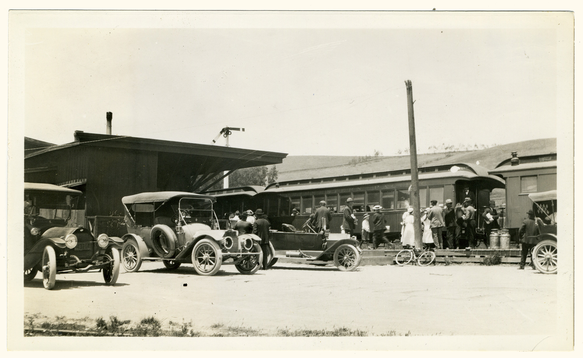 A small crowd meets the train, with cars and a bicycle, at the Tomales Depot west of Carrie Street. Circa 1920s photo by Ella Jorgensen.