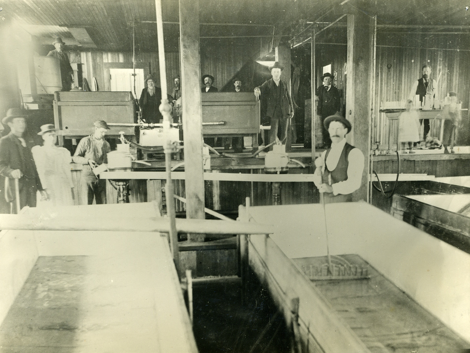 Interior of the Fallon Creamery, one of the region's largest creamery operations, with owners, workers, and probably some family members, circa 1900.