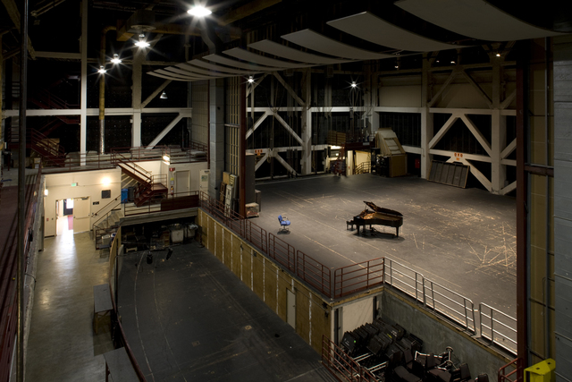 Photograph of unmodified rehearsal venue from front of house side, showing door to the street, orchestra pit installation space, and main venue with proscenium.