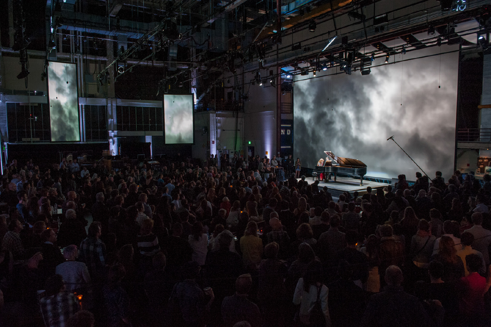 "SoundBox venue during performance, taken from within main venue. Visible hanging microphones are part of Meyer Constellation acoustic sound system, processing natural sound into a flexible virtual acoustic ""cloak"" for the room."