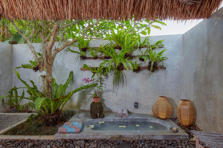 open air bathroom with sunken terrazo tub