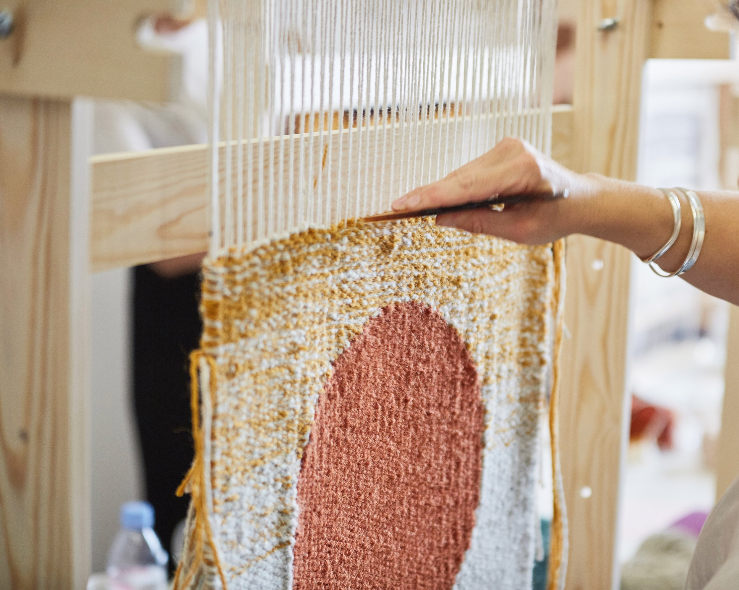 Beating down the weft to create a solid woven surface