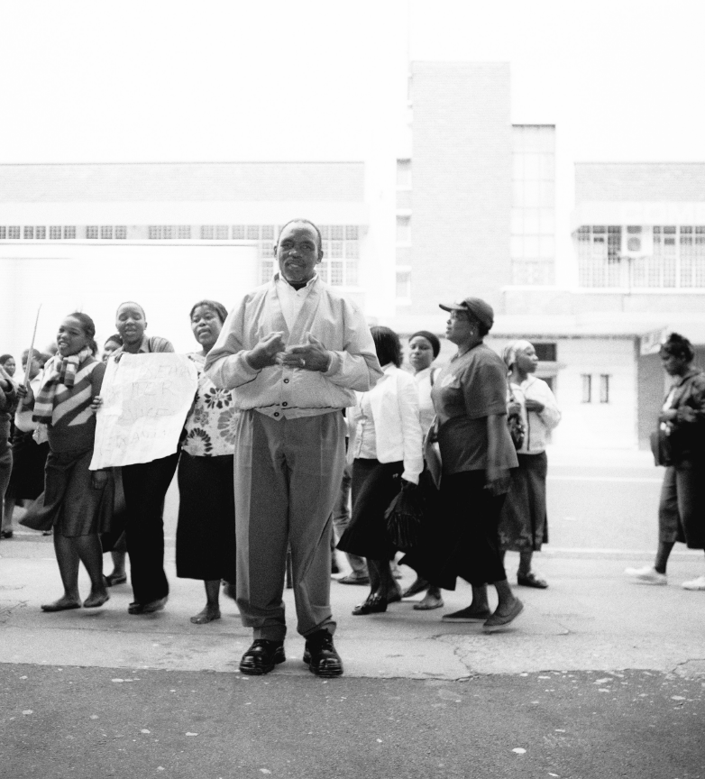Andrew Mndeni Joyisa amongst protesting clothing workers outside Bolton Hall, Gale Street, Durban.