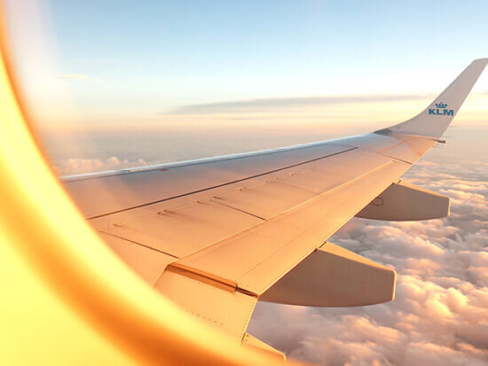 View-of-plane-wing-out-the-window-at-sunset-550x413.jpg