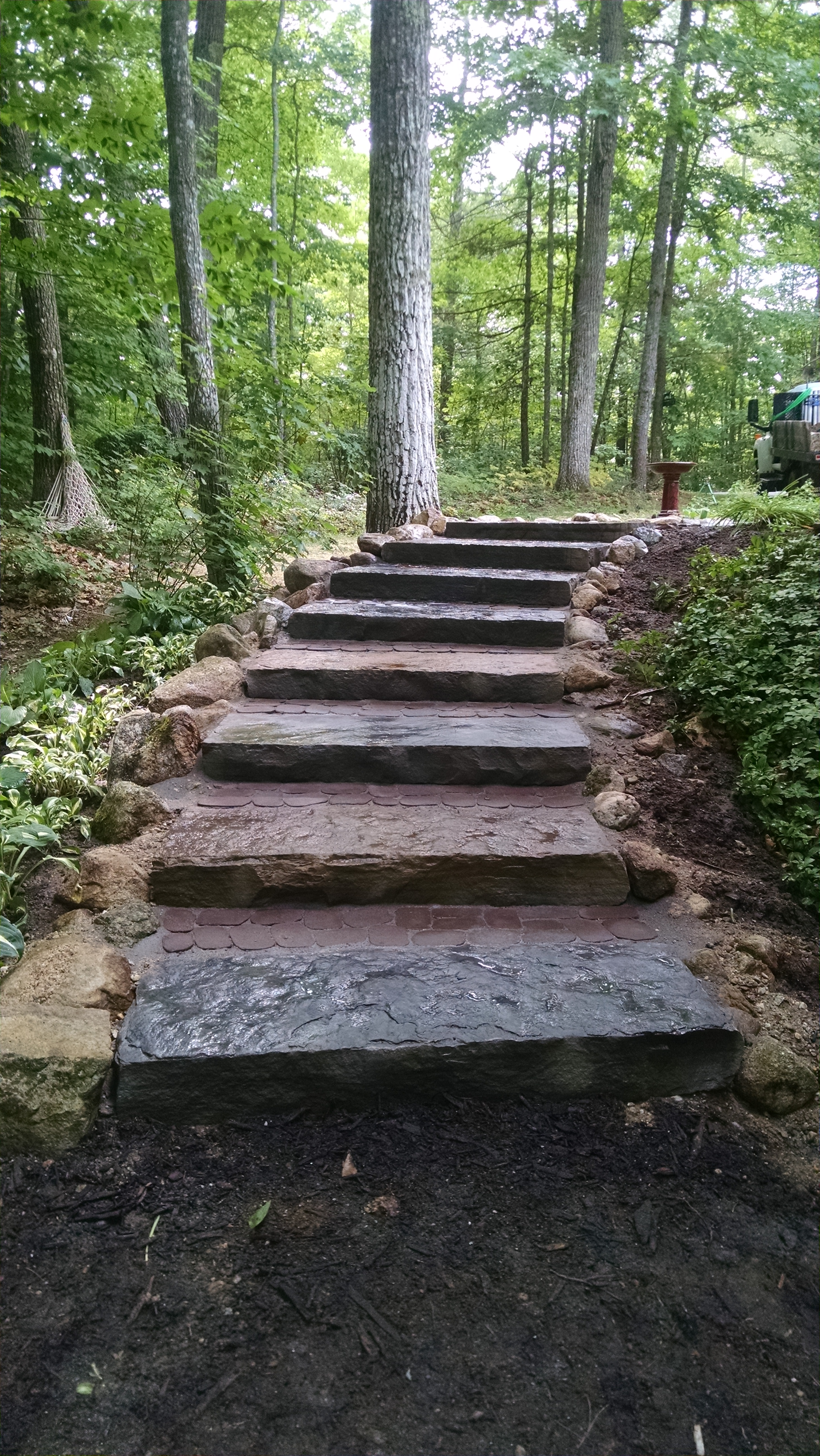 A highly erosive, worn-out path to LIttle Sebago Lake in Gray, Maine, was transformed into a functional, non-eroding, safe and durable staircase using natural stone steps reinforced with rocks and shade-tolerant ground-cover vegetation. PHOTO: Bourne Landscaping
