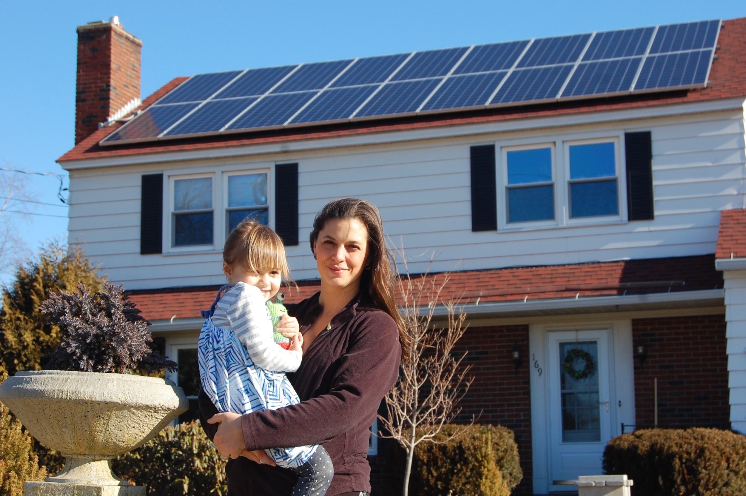 Serena Graham stands outside her Waterville home with her daughter, below the solar-electric system she had installed in the fall of 2015. The system is designed to generate enough power over the course of a year to offset the home's electric demand. Getting to net zero, she said, has always been her goal. Photo: David Angelini