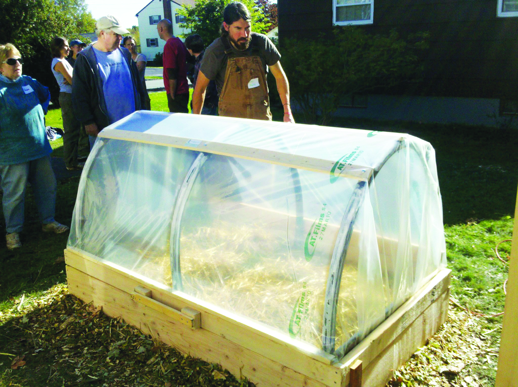 David Homa, of Post Carbon Designs, demonstrates his signature hinged hoophouse which has more ground clearance than other standard cold frame designs, leaving more room for higher-growing crops or a second layer of coverage, such as straw or Reemay. Photo courtesy of Post Carbon Designs