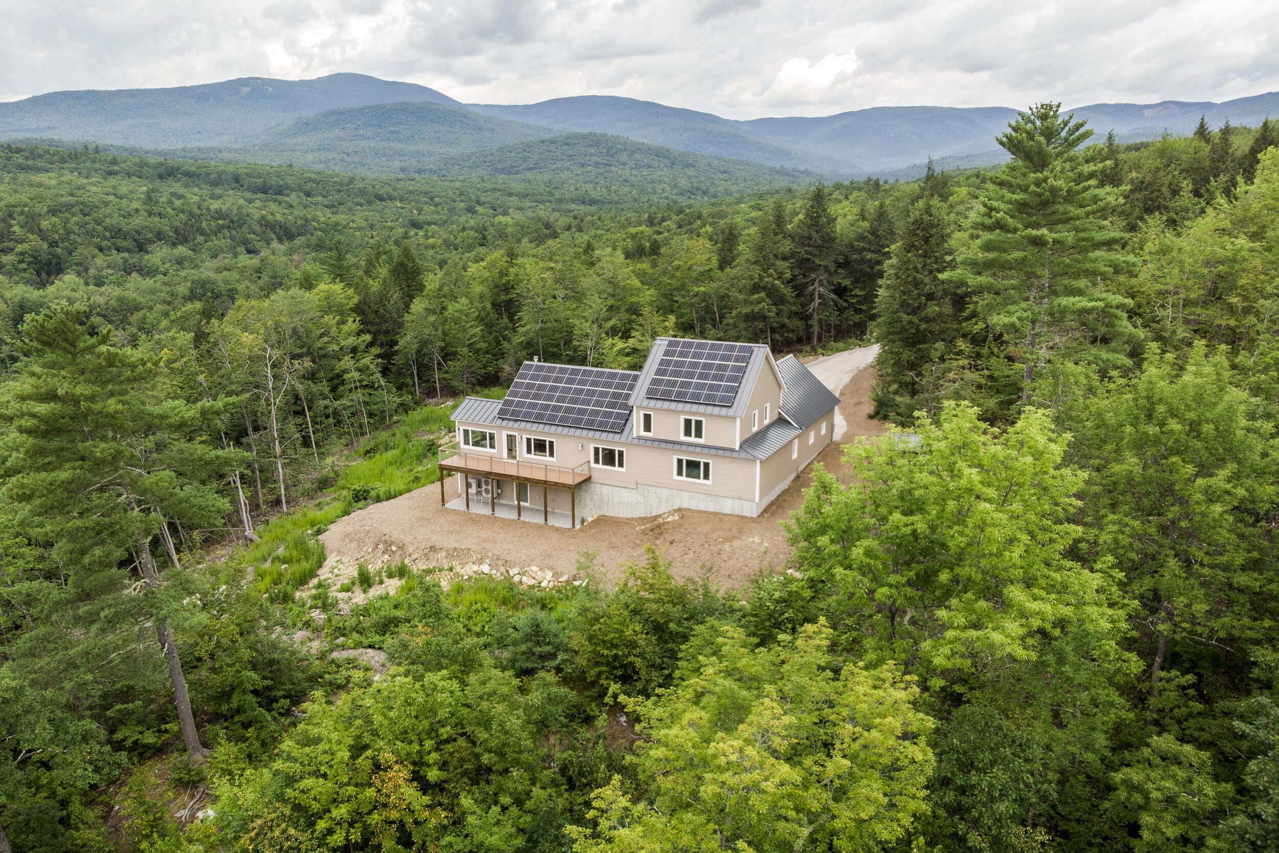 A hilltop site overlooking Kezar Lake in western Maine proved the perfect spot for a home assembled from prefabricated parts. Thanks to a 15 kW solar array, the building should generate more power than it consumes on an annual basis.