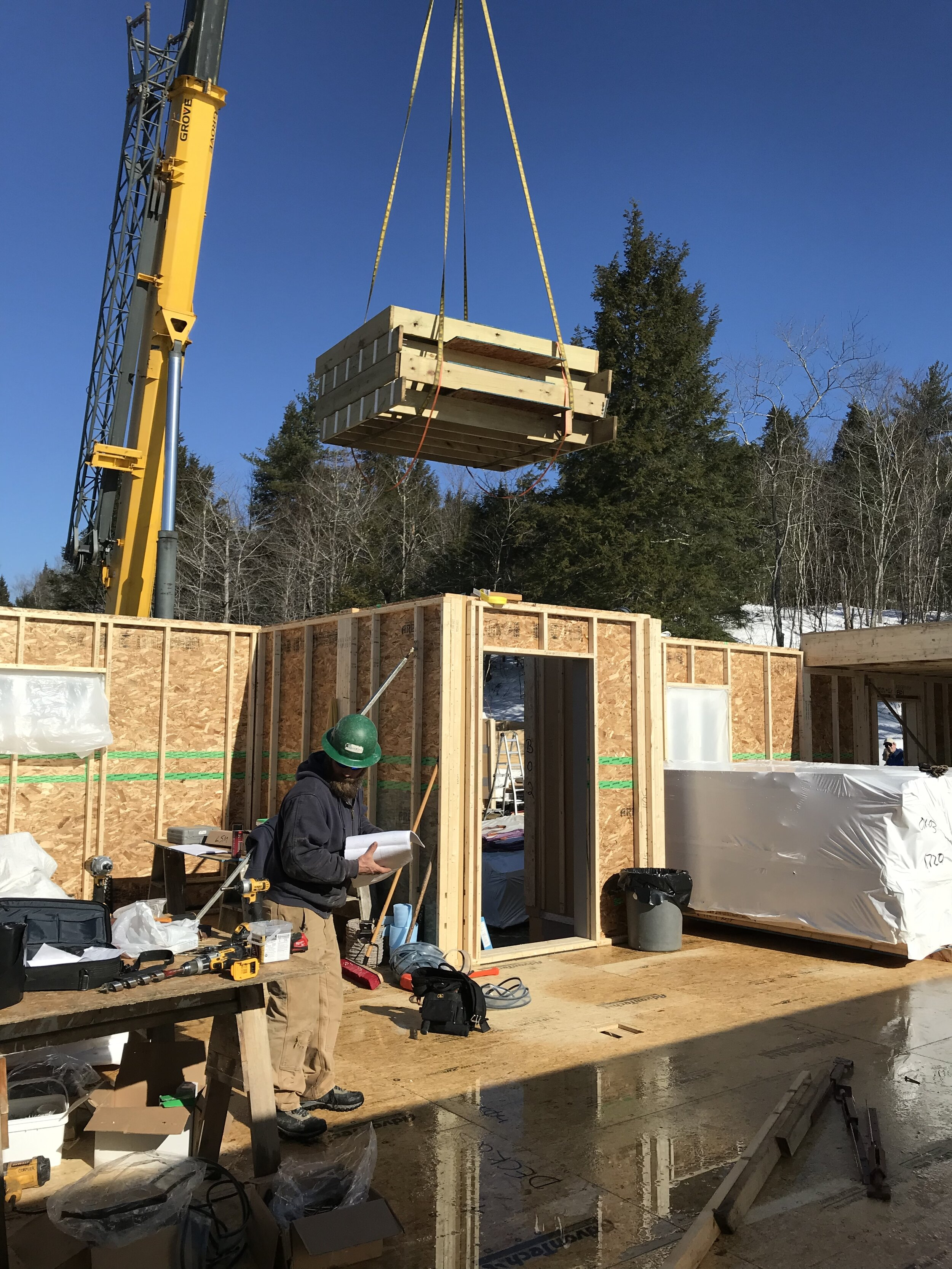 Floor and wall panels built at New Hampshire-based Bensonwood were craned into place and assembled in a fraction of the time it would have taken crews to build the house conventionally.  Photo courtesy of Mottram Architecture.