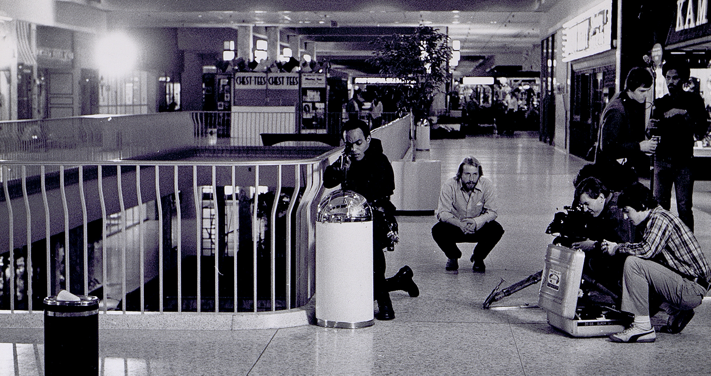 """Ken Foree (far left), the main protagonist of George A. Romero's 1978 film """"Dawn of the Dead,"""" crouches behind a trash can during filming in Monroeville Mall. From the George A. Romero Collection at the University of Pittsburgh's University Library System, Archives & Special Collections."""