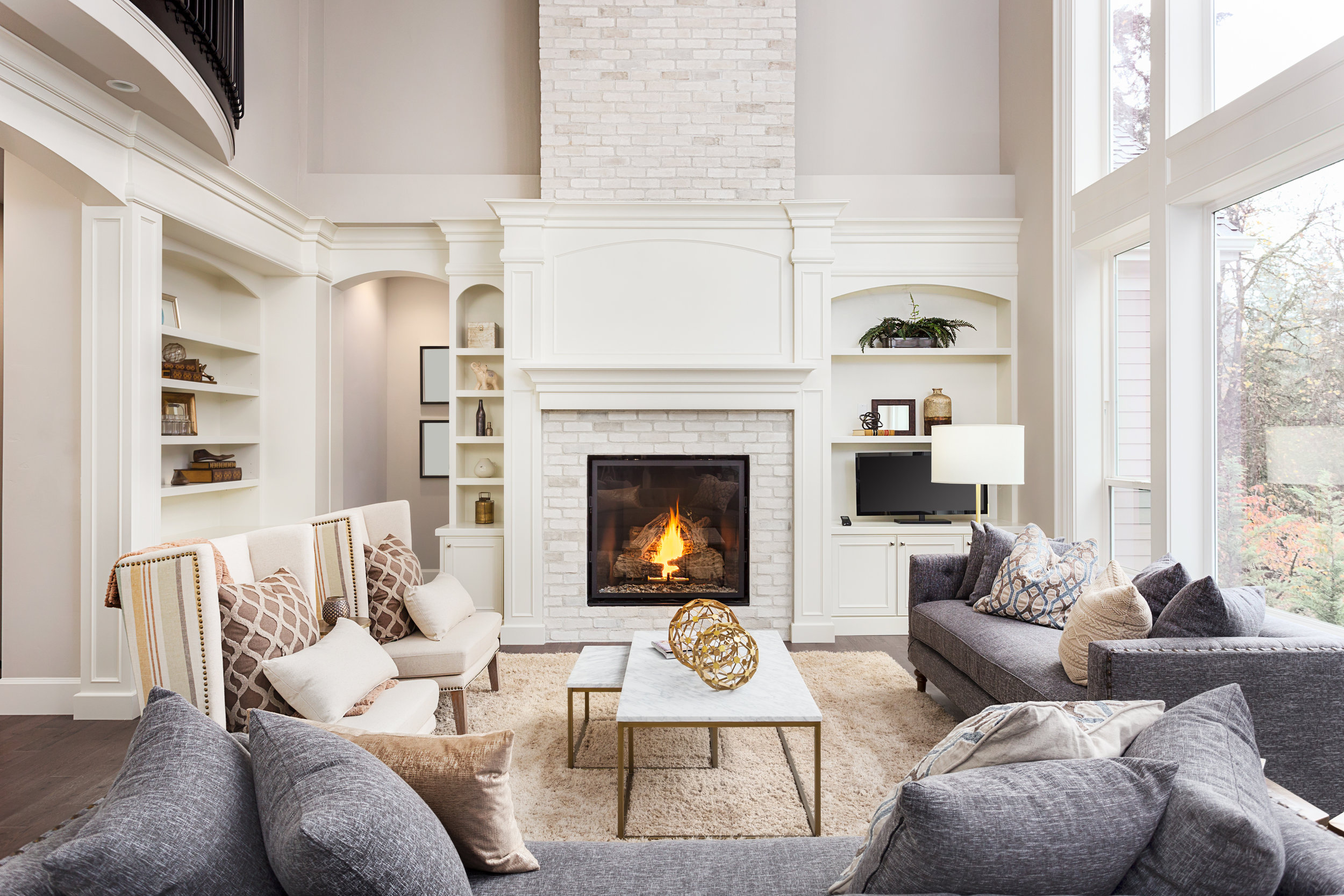 Beautiful Living Room in New Luxury Home with Fireplace and Roaring Fire. Large Bank of Windows Hints at Exterior View