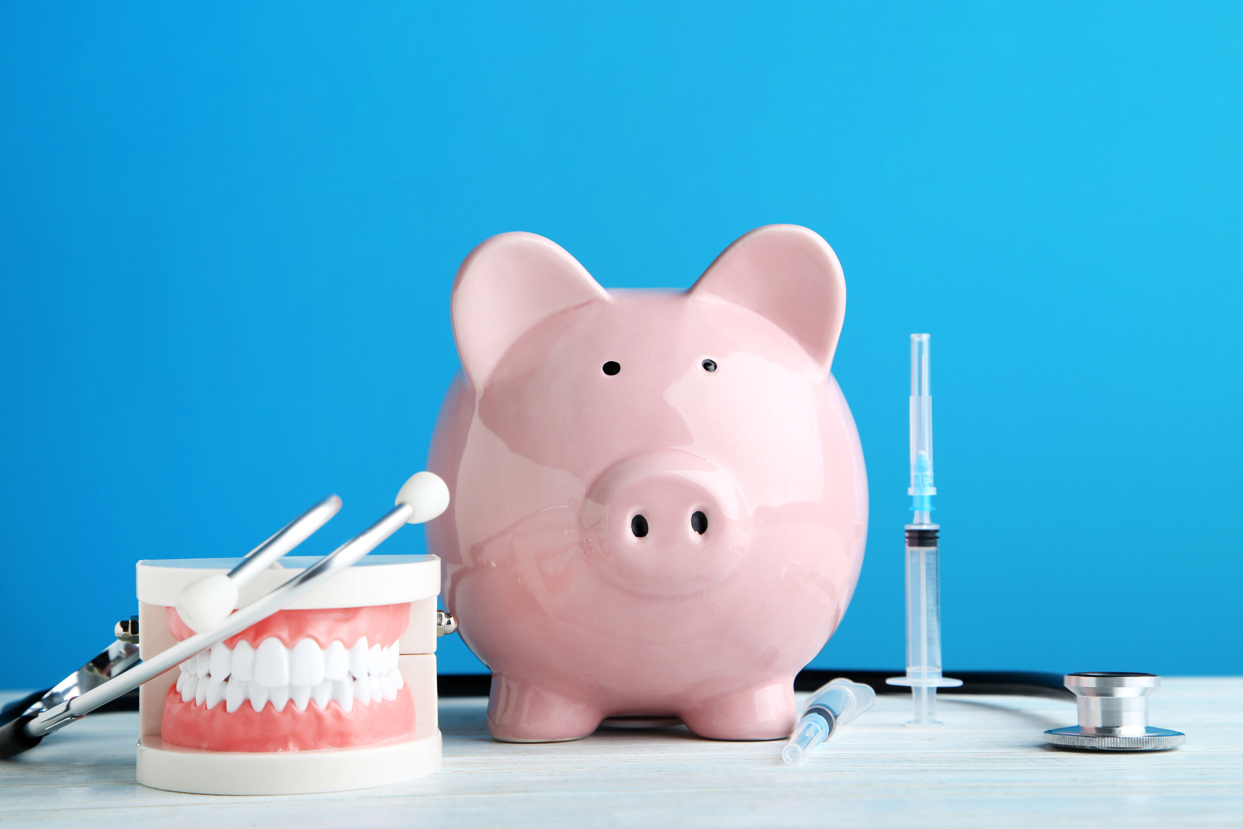 Pink piggy bank with stethoscope, syringe and teeth model on blue background