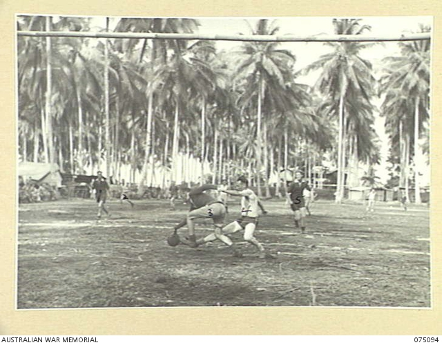 MILILAT, NEW GUINEA. 1944-08-06. A TENSE MOMENT DURING THE SOCCER MATCH BETWEEN TEAMS FROM THE 4TH INFANTRY BRIGADE AND HEADQUARTERS, 5TH DIVISION DURING THE FIRST GAME PLAYED ON THE NEW HEADQUARTERS SPORTS OVAL. IDENTIFIED PERSONNEL ARE:- N211492 CORPORAL M.A. HAKAINSEON (2); B419 SENIOR REPRESENTATIVE R.G. SCOTT, AUSTRALIAN RED CROSS SOCIETY -