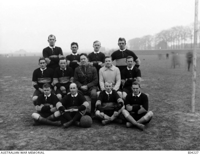 An outdoors group portrait of unidentified members of the 1st grade soccer team of the 9th Battalion and an unidentified officer, on a playing field. - Belgium: Wallonie, Hainaut, ChateletFirst World War, 1914-1918