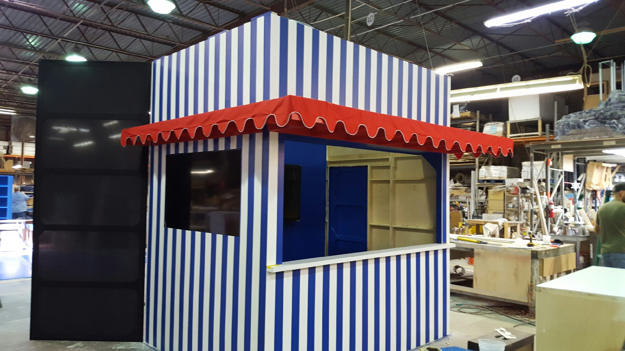 Striped booth with red awning – constructed the awning. Created the scalloped drop. It is piped in white. Had to do the math to make the scallops the right size.