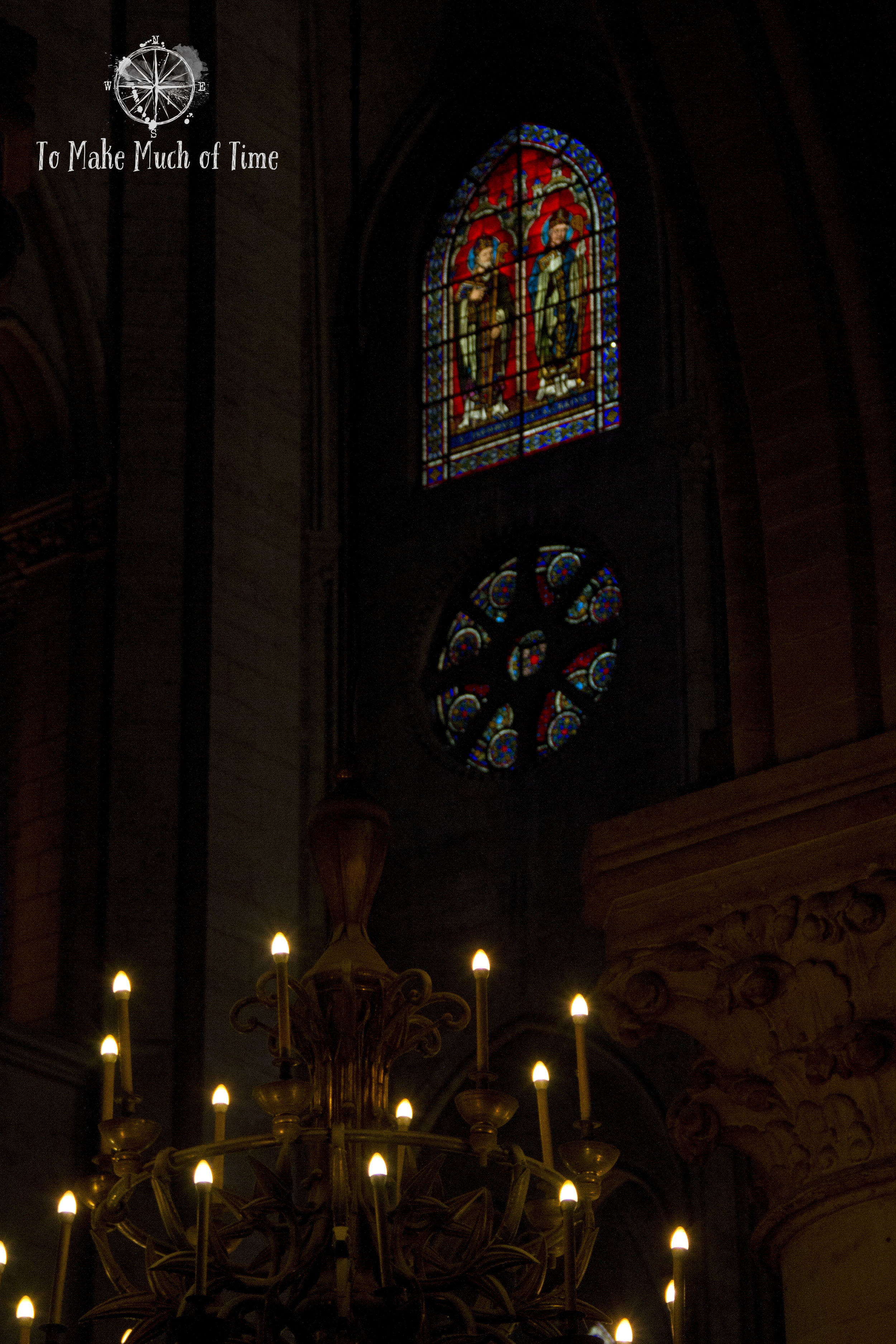 Inside Notre Dame is dark but amazing colors shine through the stained glass windows.