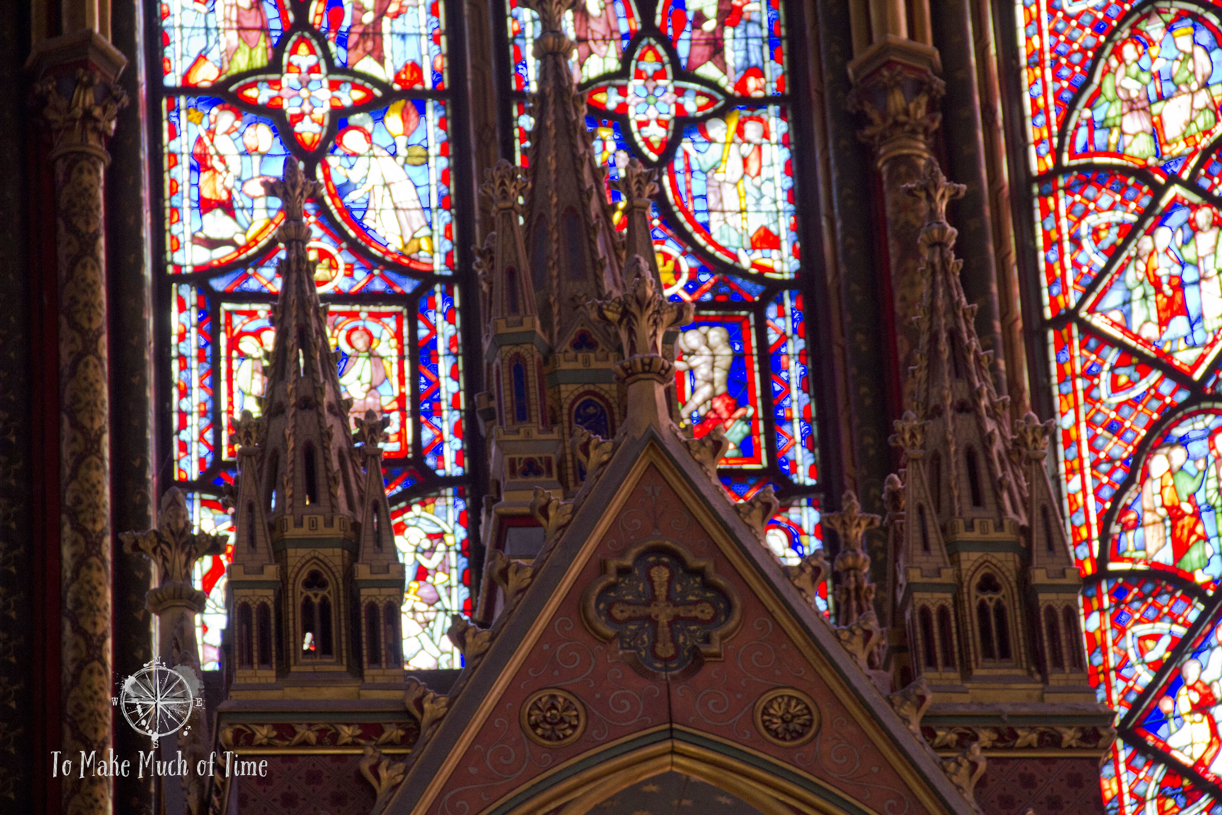 Part of the alter at Sainte-Chapelle with stained glass windows as its backdrop.