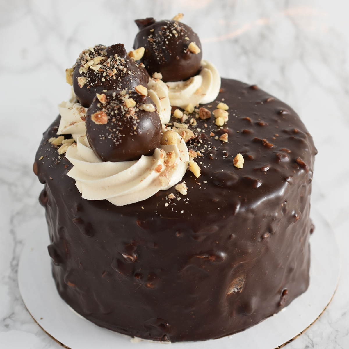 Ferrero Rocher - This decadent cake is based off the infamous Ferrero Rocher chocolates. Moist chocolate layers, Hazelnut crunch ganache inside and of course hazelnut frosting. On top you'll find hand rolled hazelnut cakepops.Gluten Free option available