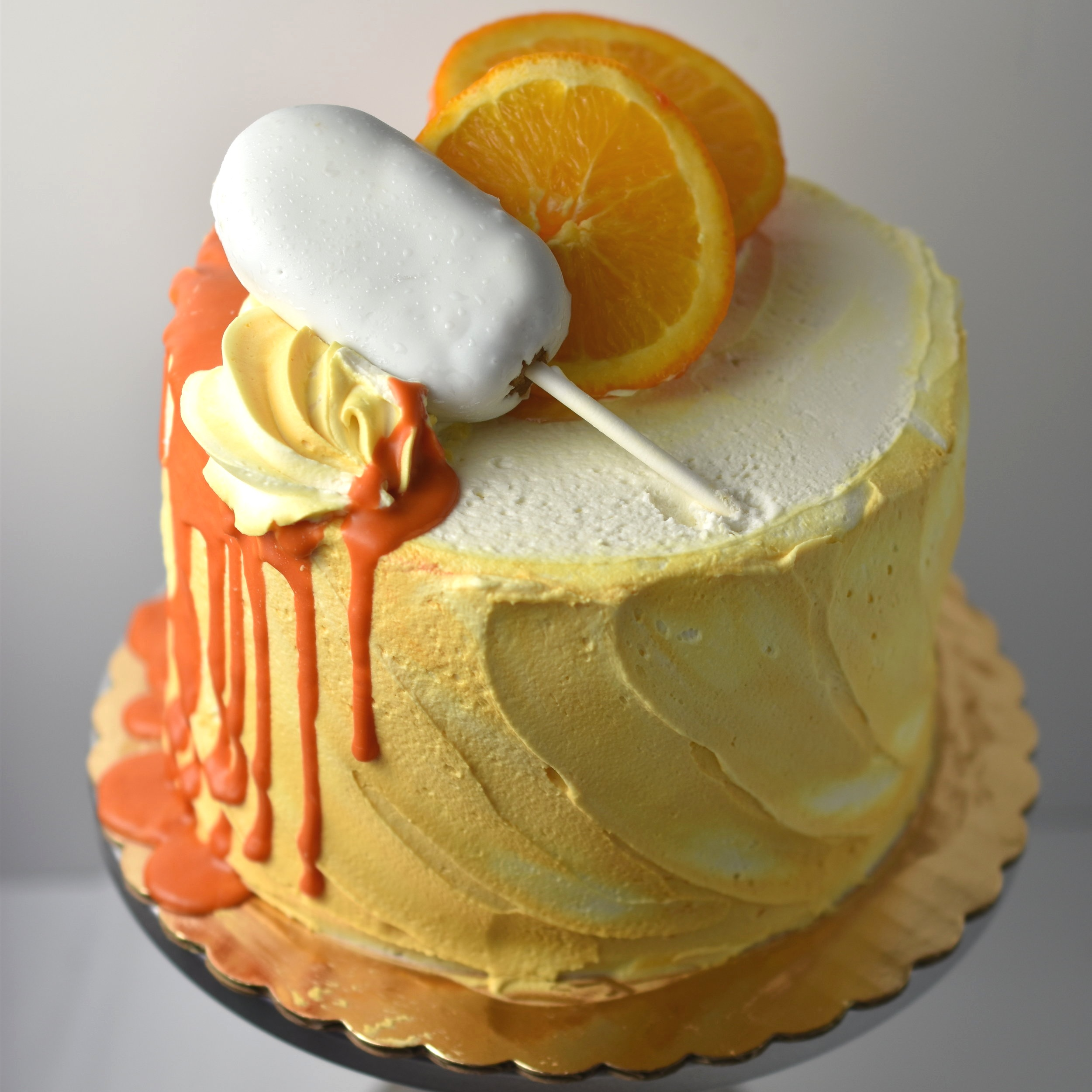 Orange Creamsicle - If this cake doesn't scream summer than I don't know what does! Our homemade vanilla cream fills layers of moist vanilla cake. This handsome devil is then finished off with an orange zest buttercream.
