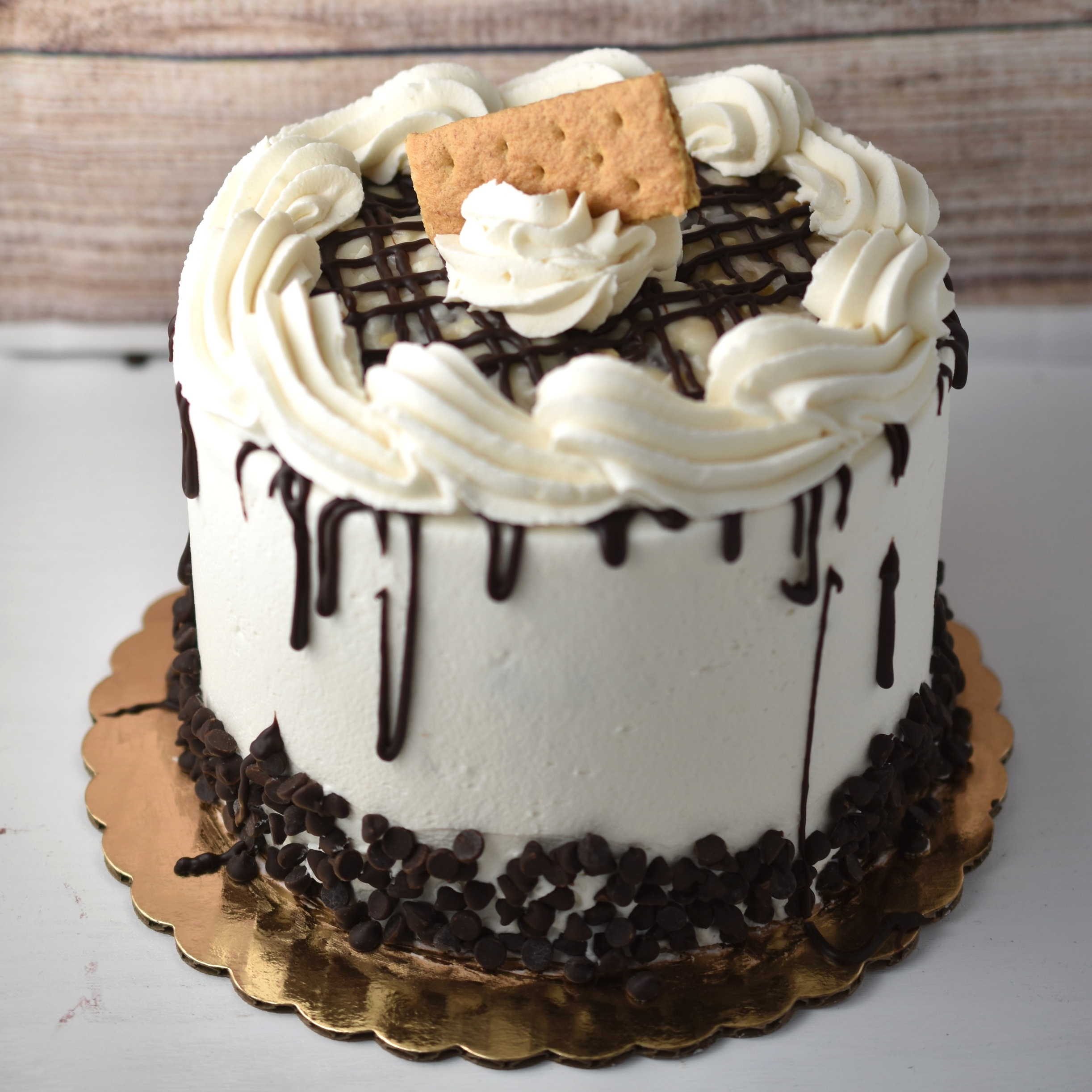 Magic Bar - This cake is inspired by our popular Magic bars. We have created a magical filling made up of coconut, chocolate chips, white chocolate, and peanuts. This tasty filling is then sandwiched between vanilla cake layers and frosted with whipped coconut frosting.
