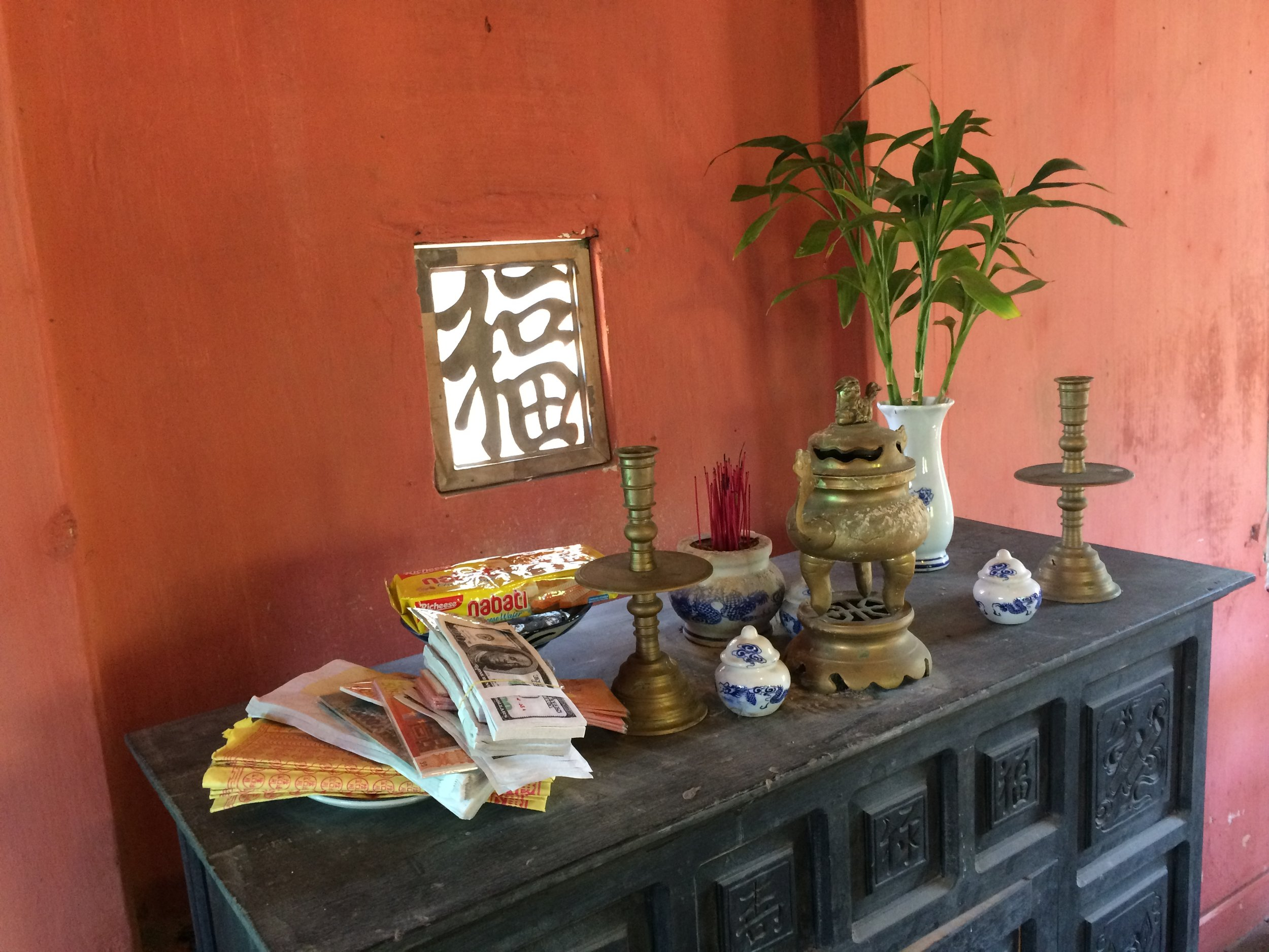 Offerings in a second-floor shrine at a café in Hội An, Việt Nam.