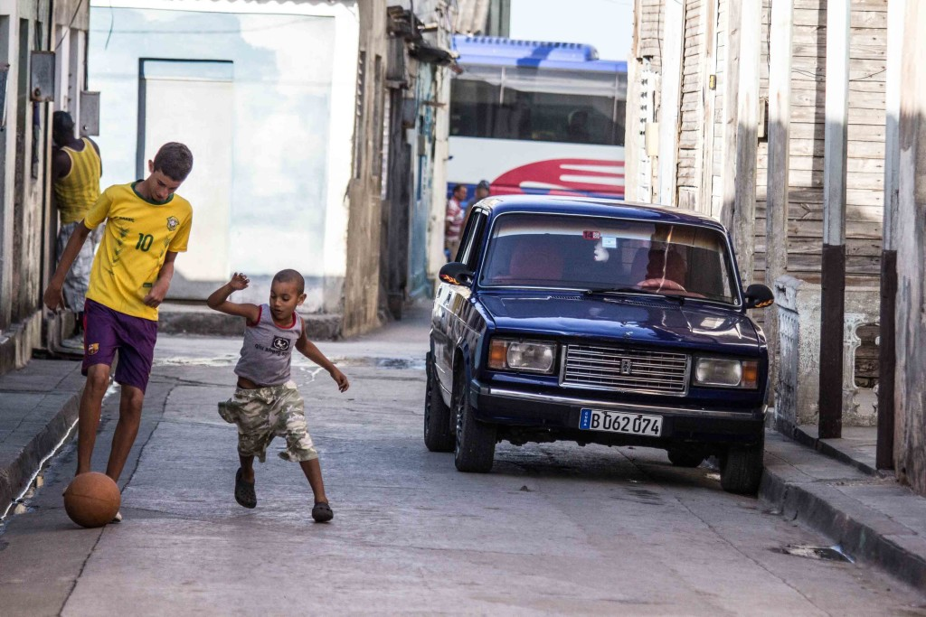 Children are playing with a ball near the car