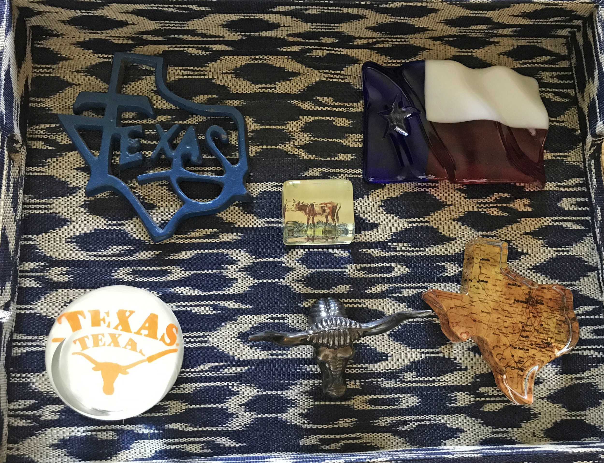 In another tray my client displays Texas paperweights. Paperweights are one of my favorite things to collect because they are affordable and come in so many shapes and sizes. Collecting with a theme is so much fun and makes gift giving super easy.