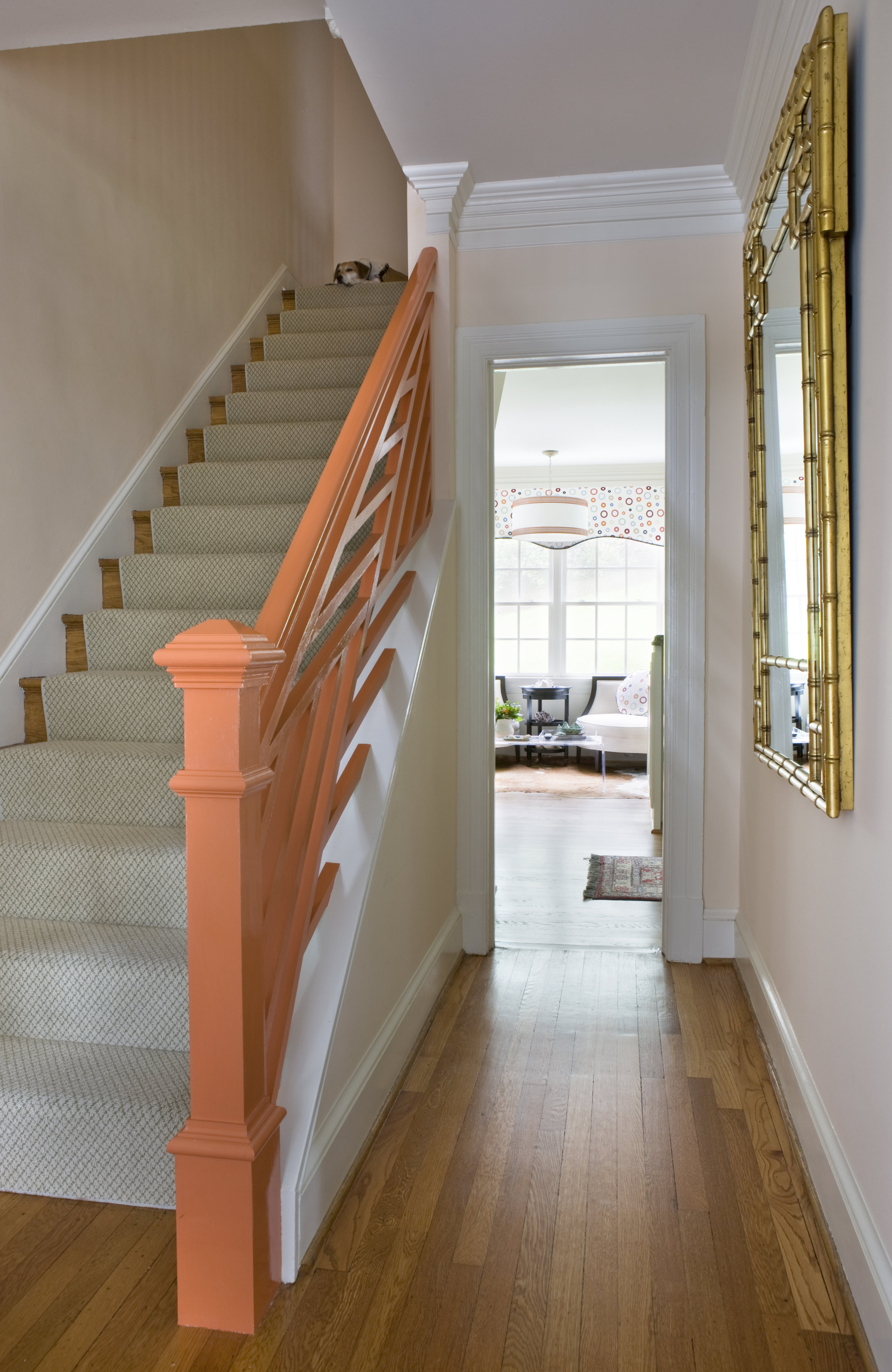 The custom light in the kitchen seating area pairs nicely with the custom railing painted coral in the foyer of this fun home.