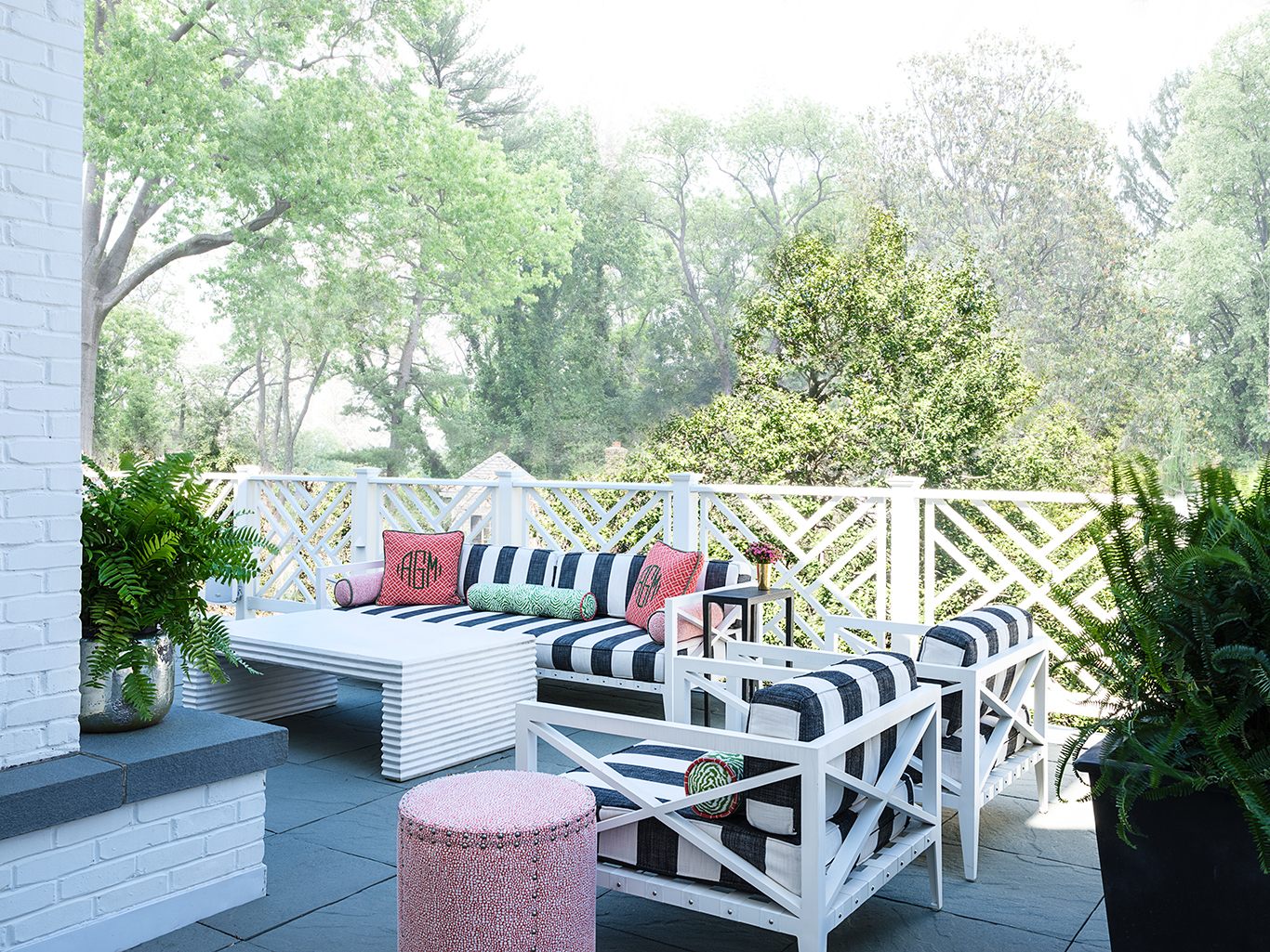 Here, the more muted tones allow the coral to really pop and make this terrace space inviting.