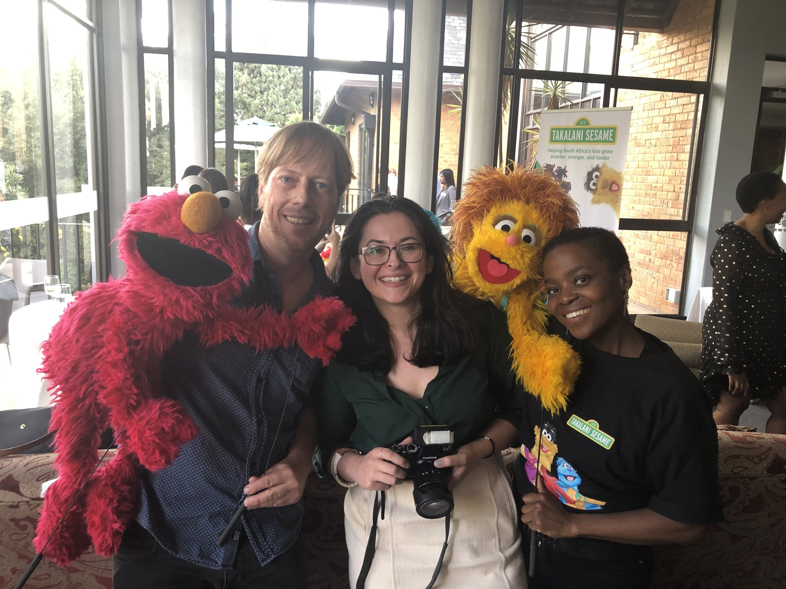 Bettina (in the middle with a camera) poses with two puppateers and their puppets from the Takalani Sesame production. The two puppets are Neno (Elmo for US audiences) and Kami (South Africa's HIV-positive muppet).