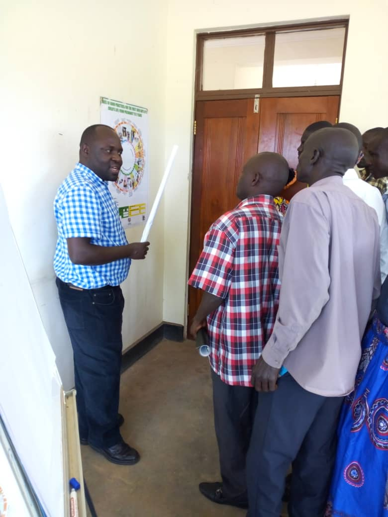 Michael Odong, SBC Advisor for USAID's RHITES,N-Lango Project in Uganda, conducts a training for Volunteer Health Teams (VHTs) of the Maternal and Child Health Wheel of Life SBC tool in Dukolo, Uganda to support interpersonal communication.  The Wheel traces the different behaviors a woman and family should follow for good health of the mother and the newborn child. VHTs will use the tool in meetings with pregnant women and new mothers in Lango. The tool was adopted from USAID's Nutri-Salud in Guatemala.