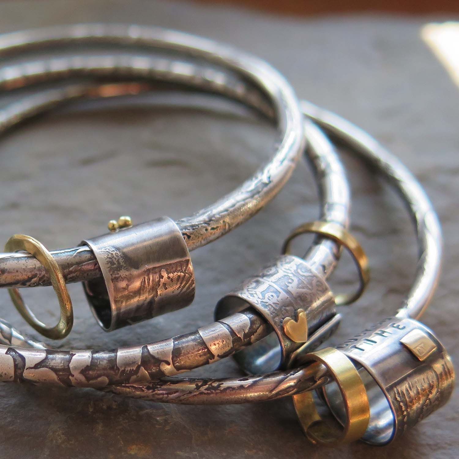 Etched and oxidised silver & gold Poetry Bangles by Ali Tregaskes