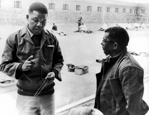 Nelson Mandela in the yard of Robben Island Prison talking with fellow prisoner Walter Sisulu, 1966.  (Photo credit: BBC)