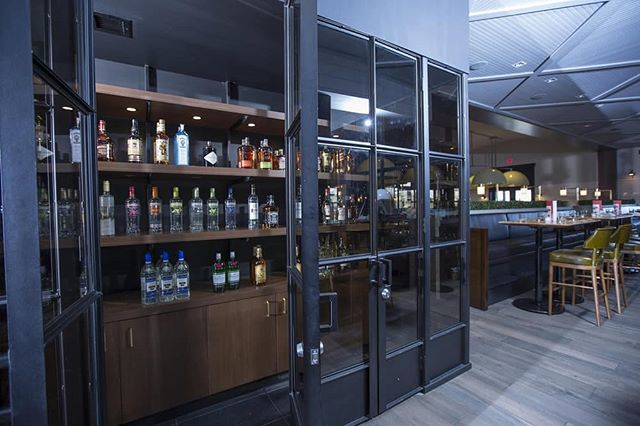 BAR RENO || The renovation we completed at @earlscrossroads in Edmonton features a sleek, glass-walled liquor room. • • • #macleodbuilt #macleodbuilders #mcleodandproud #earlskitchenandbar #earlsedmonton #bar #liquor  #glass #customglass