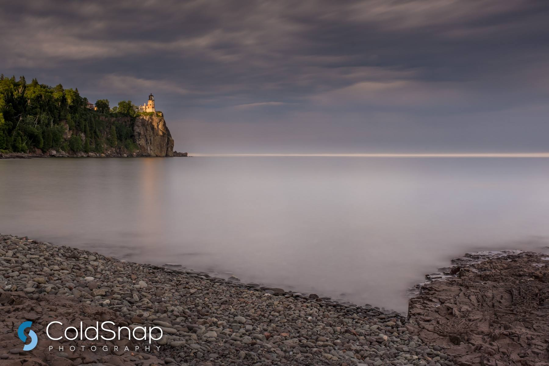 Split Rock Lighthouse and Pebble Beach at Sunset / John Gregor