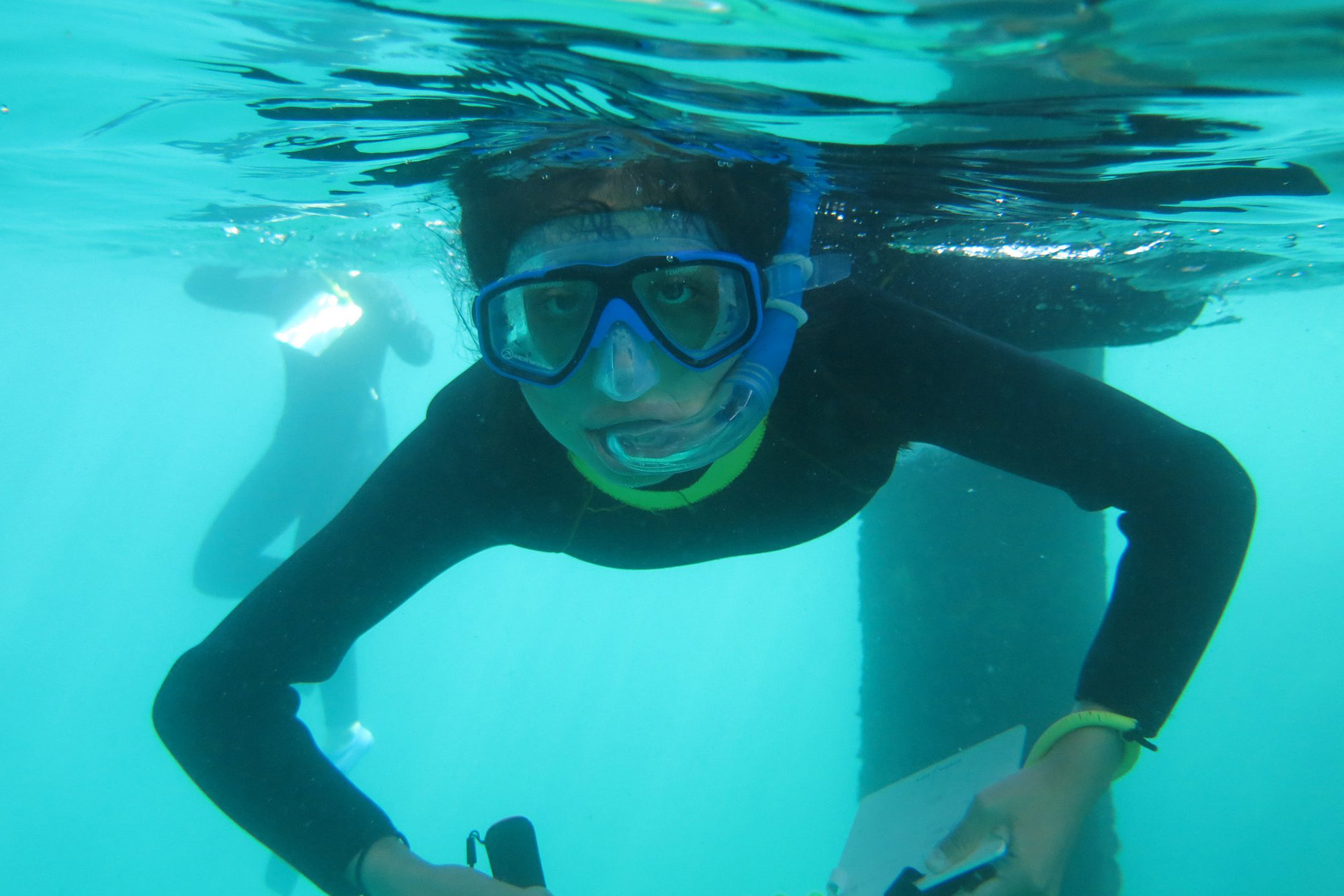 Quetzalli Vergara uses her dive slate to take measurements during her snorkel on Catalina Island as part of the Ocean Research Methods course