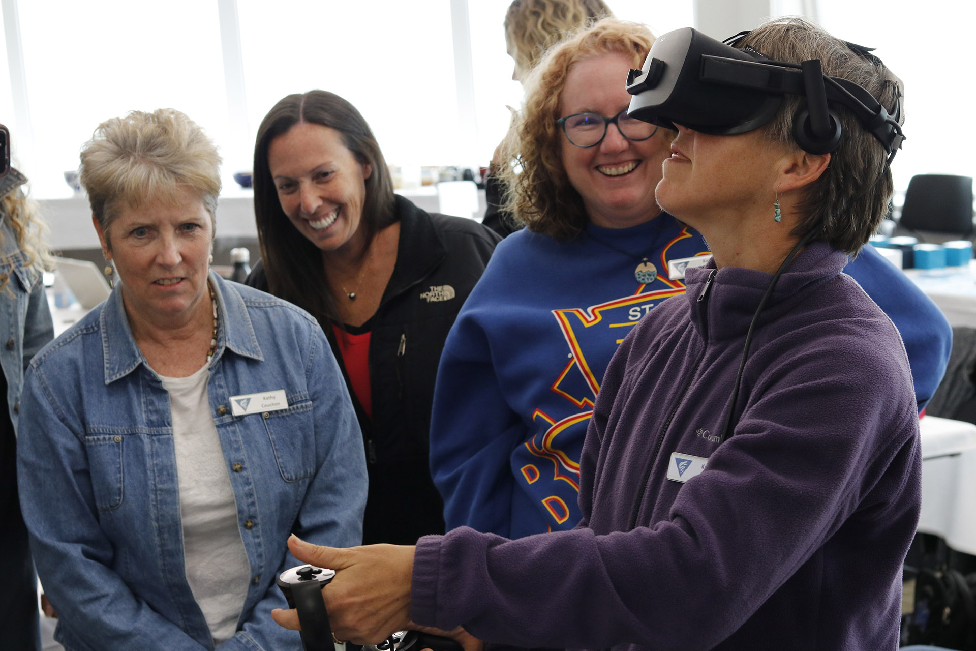 Educators watch as Kristina Vetter uses virtual reality to explore inside a giant larvacean house