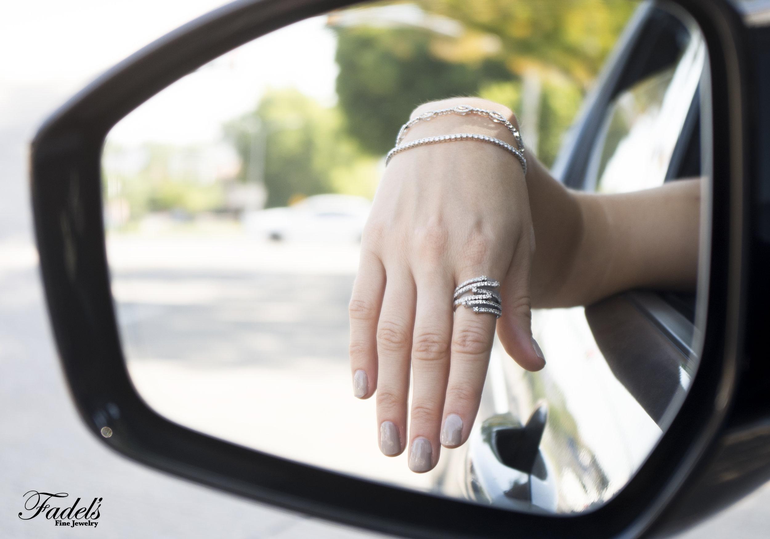 Car mirror with diamond tennis bracelet and diamond stacking ring.JPG