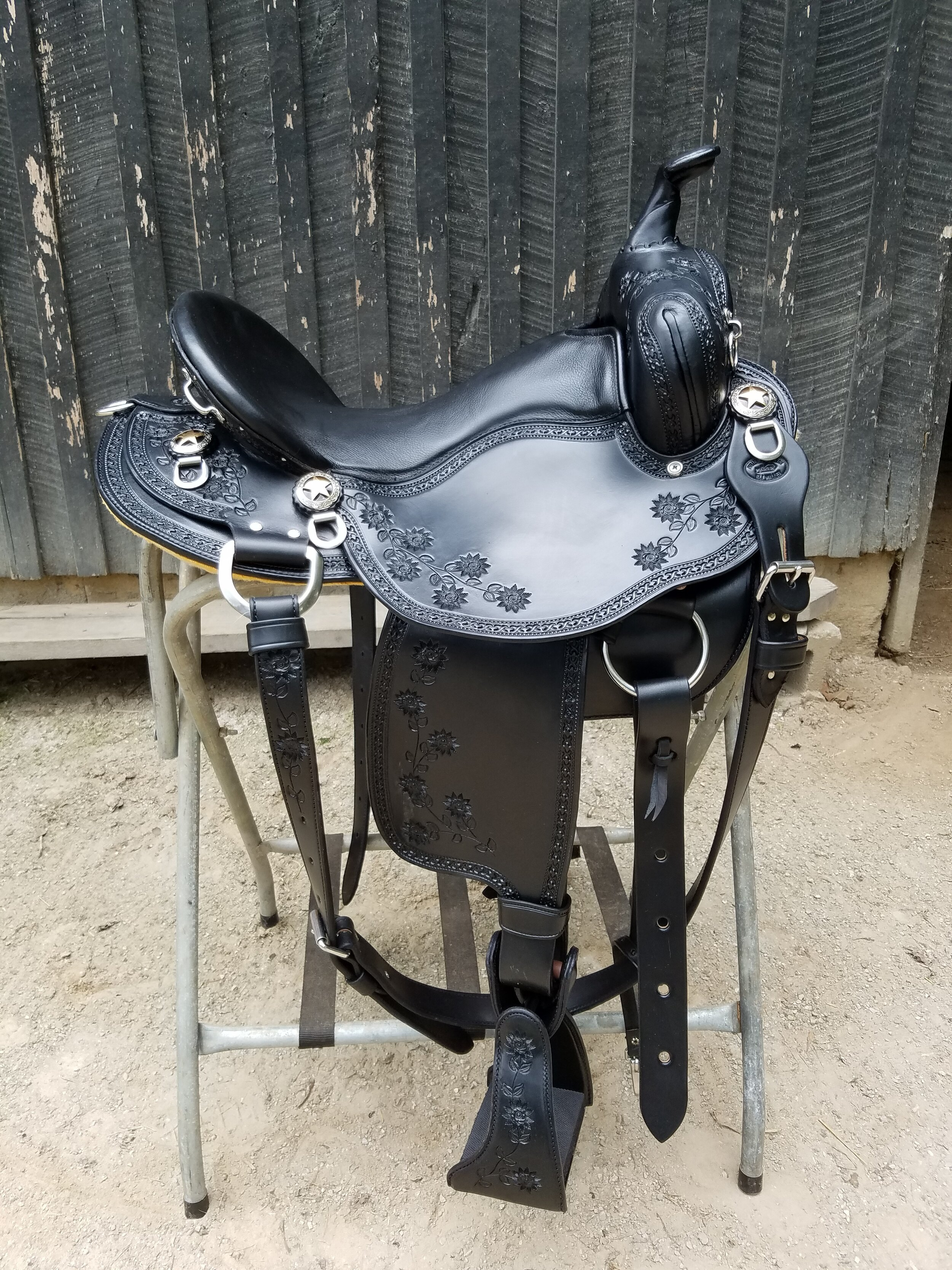 "16"" Eli Miller Custom Trail Saddle - This black beauty is perfectly accented by the floral tooling throughout. It has a 5"" cantle and suspended seat and is finished off with comfort stirrups and turners to ease you knees. It also has an added back rigging for those tough trails."