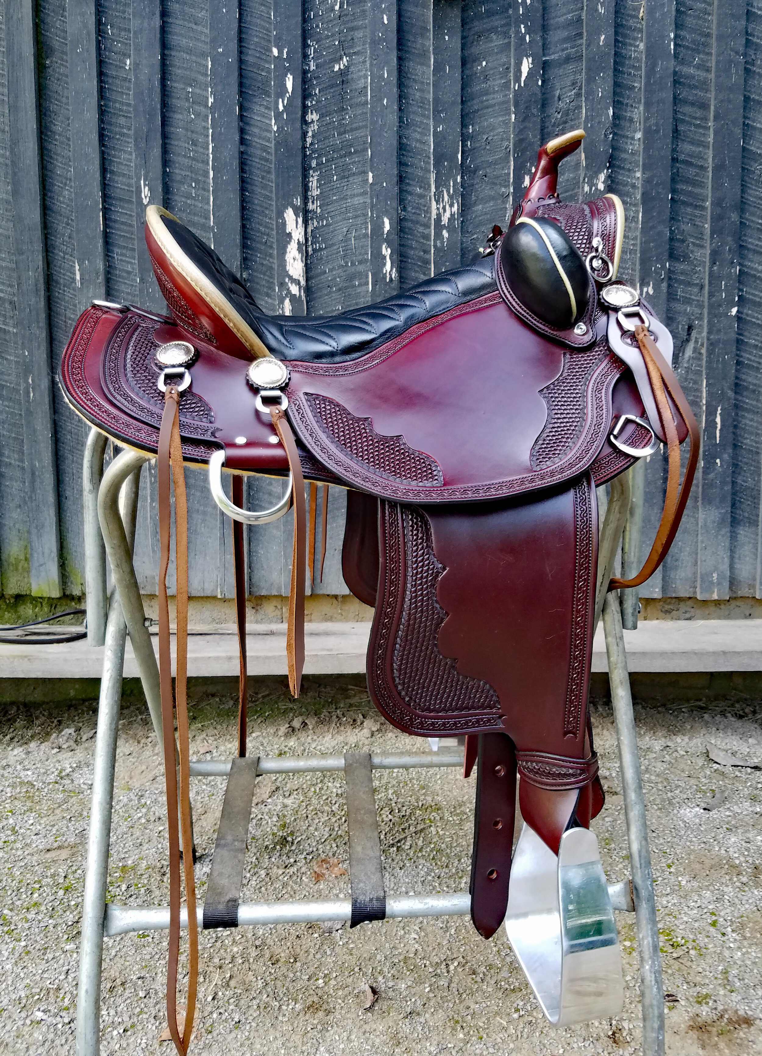 "16"" Custom Old Timer by Eli Miller - This beauty shows the double oil chestnut finish perfectly accented by the natural rawhide pencil rolls in front and back. Tilted aluminum stirrups help the knee stress as well as the twisted leathers. Bucking rolls help secure your position. Suspended seat for the comfort of the rider. Batie tree for the comfort of the horse."