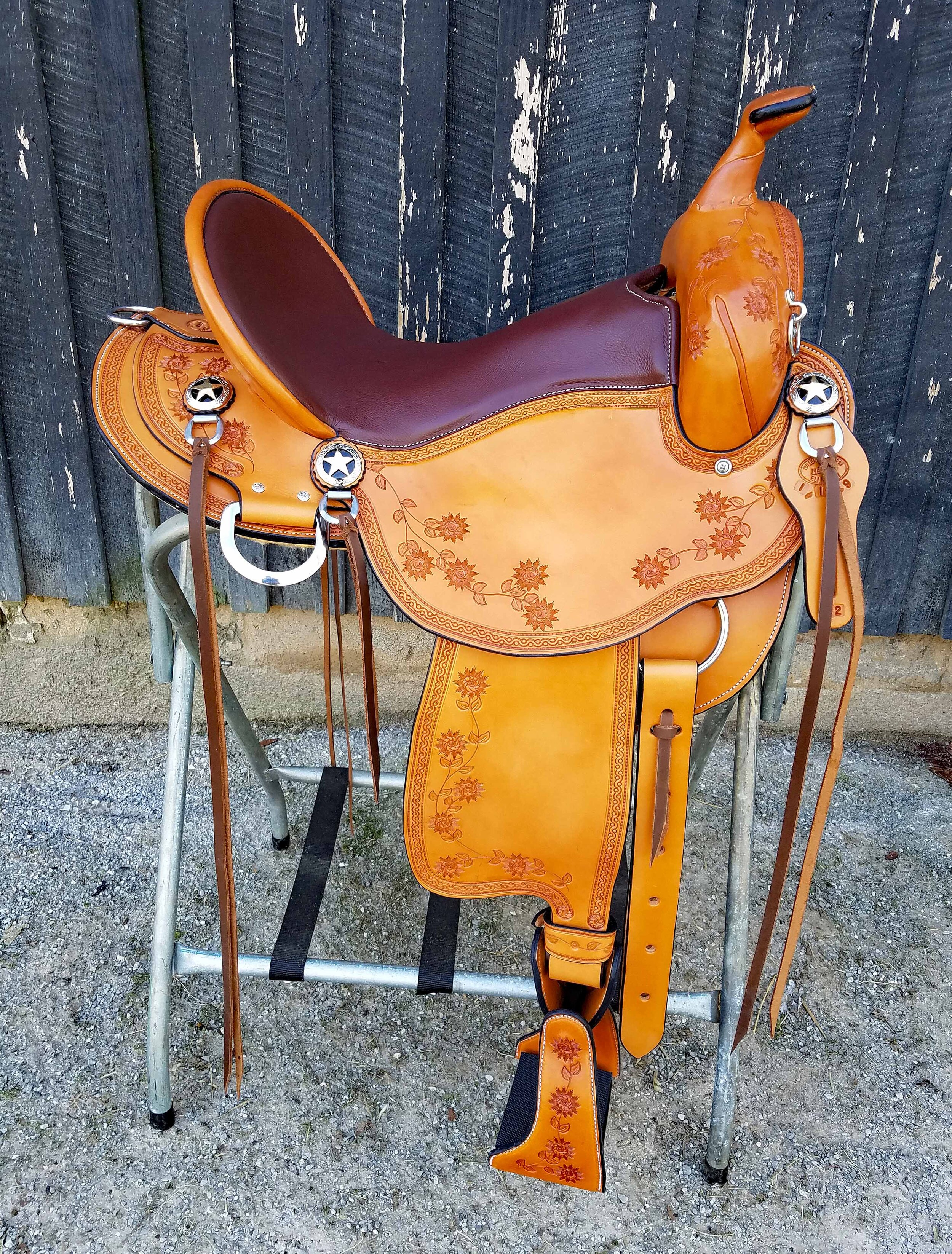 "16"" Custom Trail Saddle by Eli Miller - Looking for a standout? This saddle is it. Light pecan color highlighted with a caramel color seat and floral tooling throughout. This saddle is lightweight and oh so comfortable. The comfort stirrups and turners will ease your ride on the long trails."