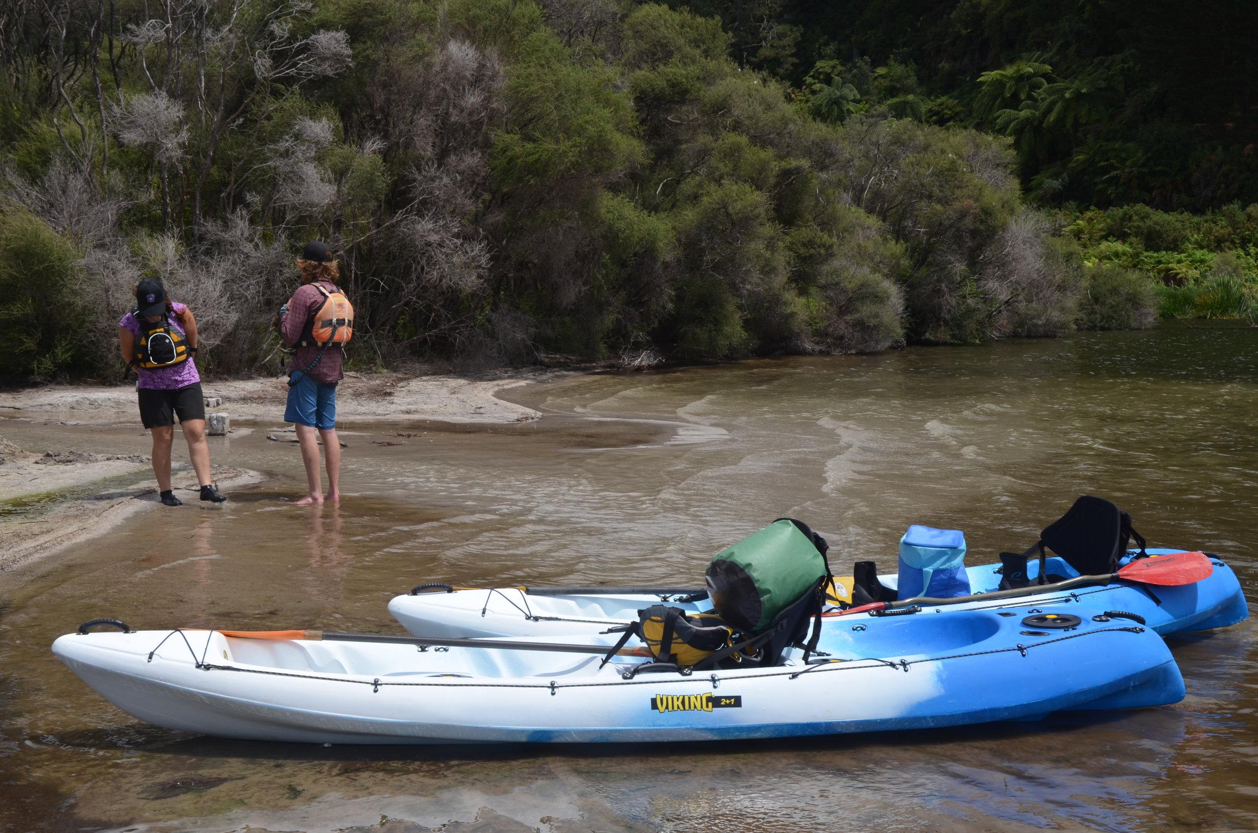 Kayak two people stand on beach.JPG